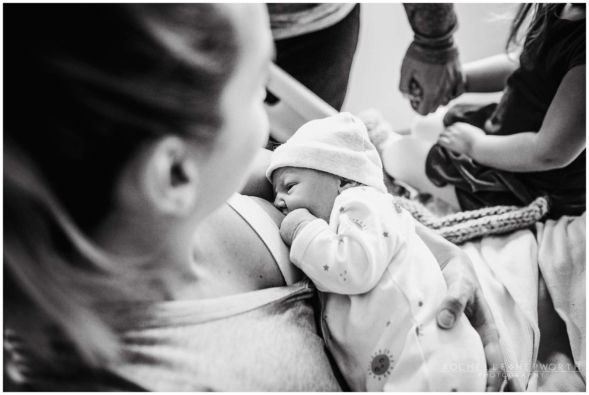 black and white photo of mom breastfeeding newborn baby