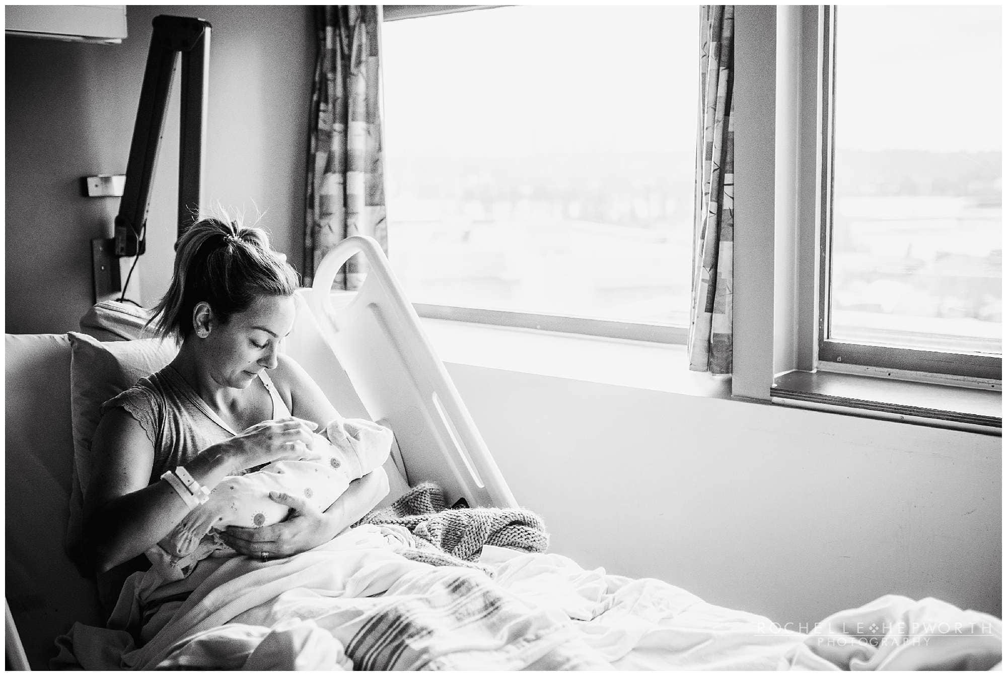Black and white photo of mom breastfeeding baby in hospital bed