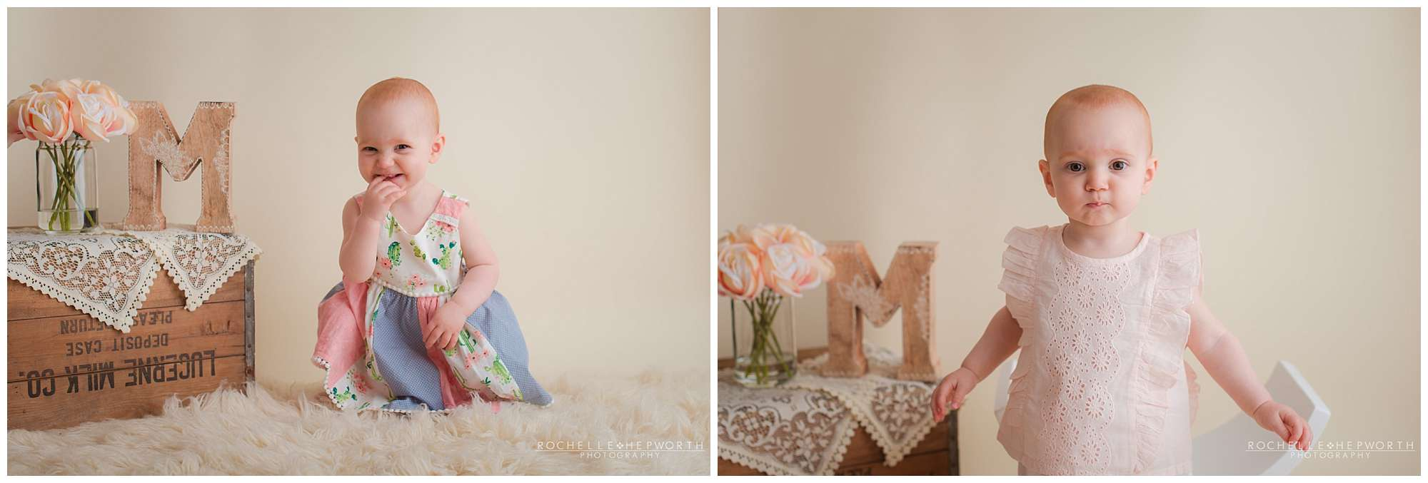 baby girl in floral dress smiling next to crate with letter M