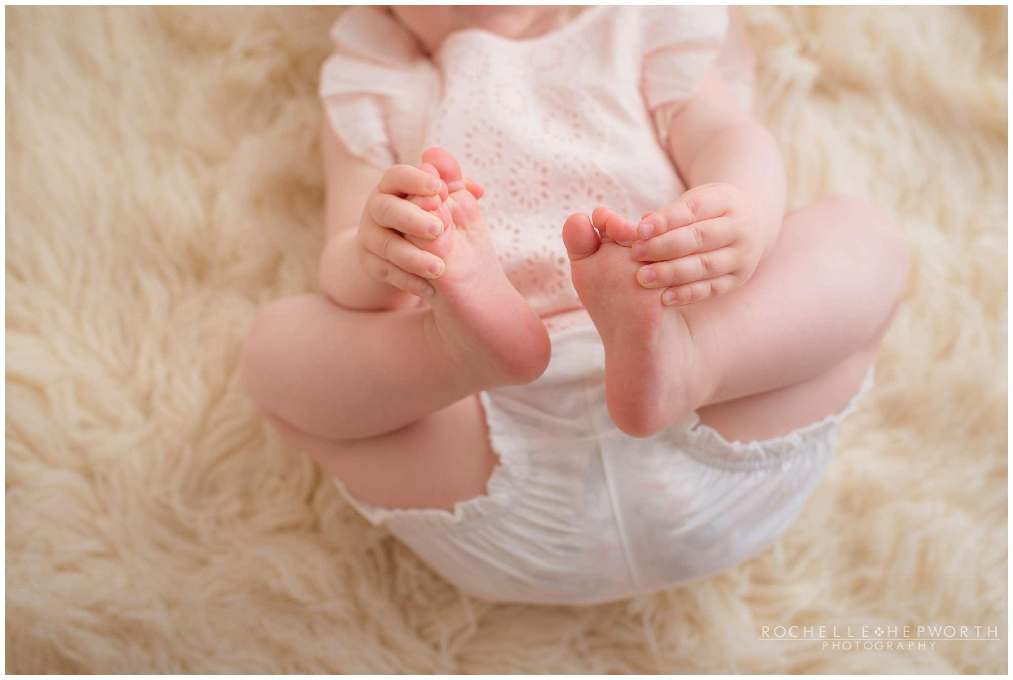 baby girl holding her feet on cream shaggy carpet