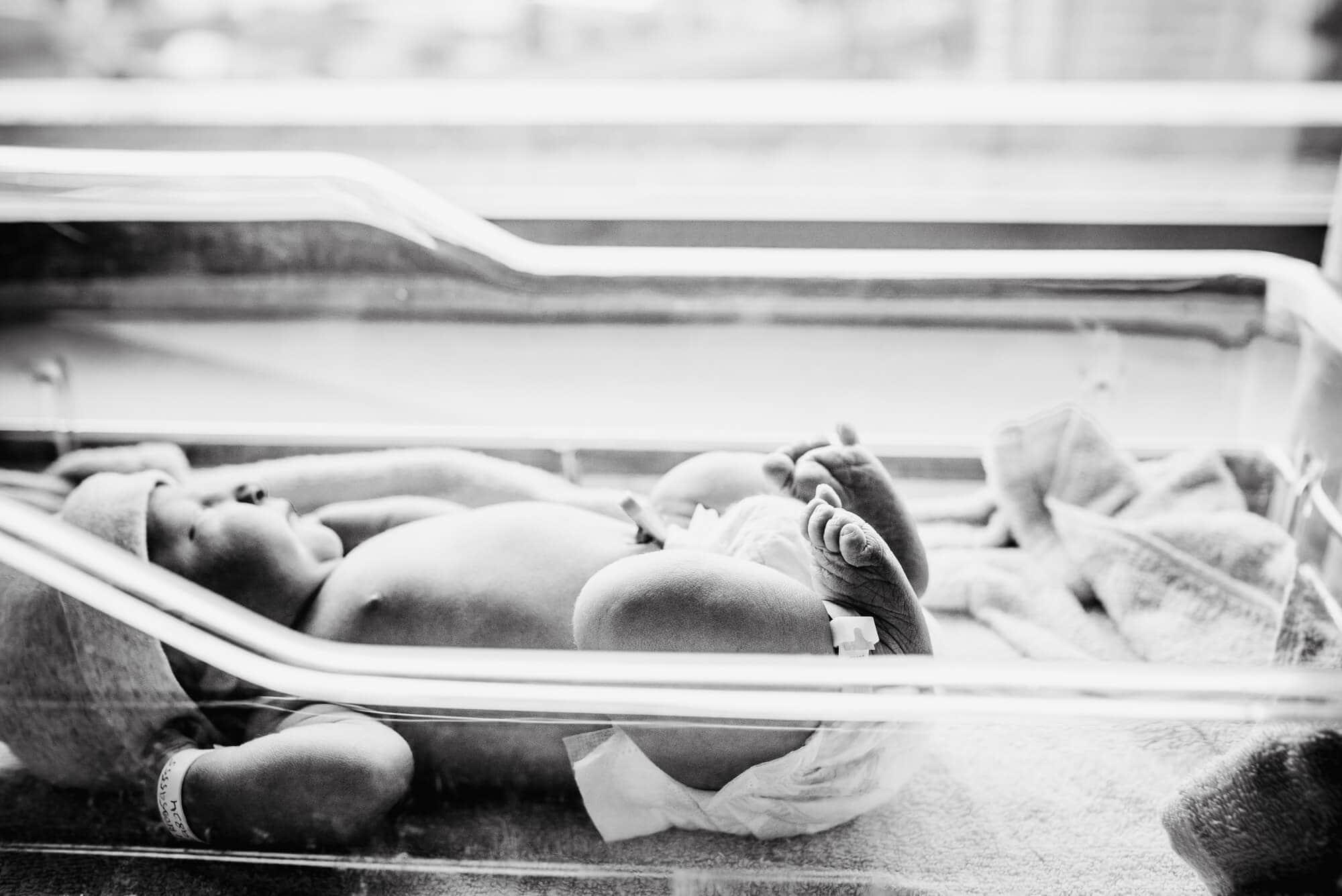 newborn baby lying in bassinet