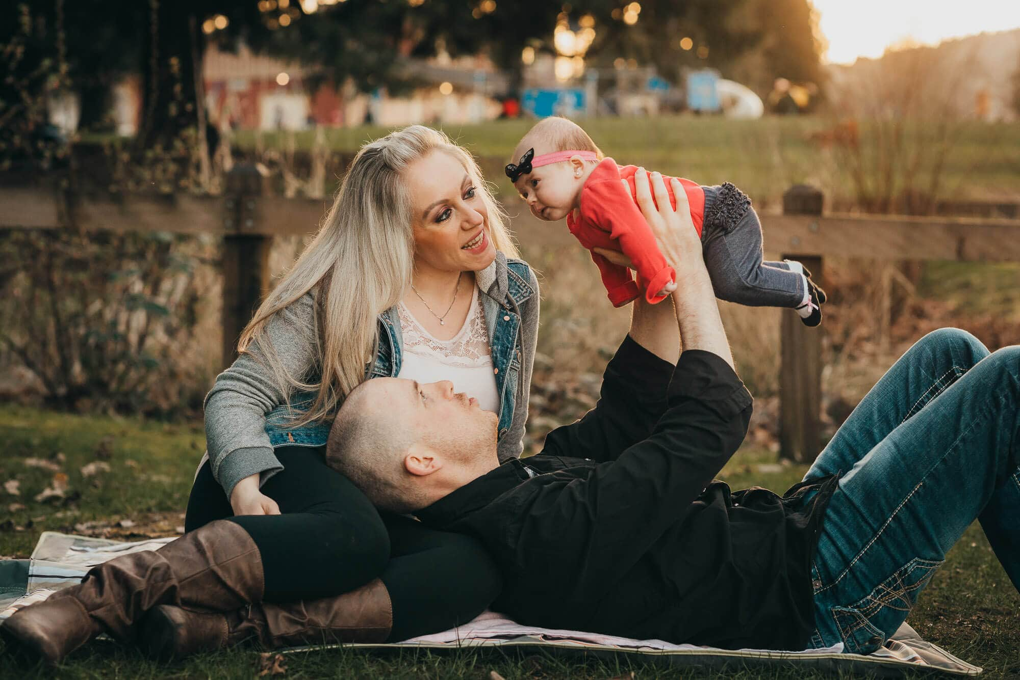 dad lifts baby while lying on mother's lap in Rocky Point family photoshoot