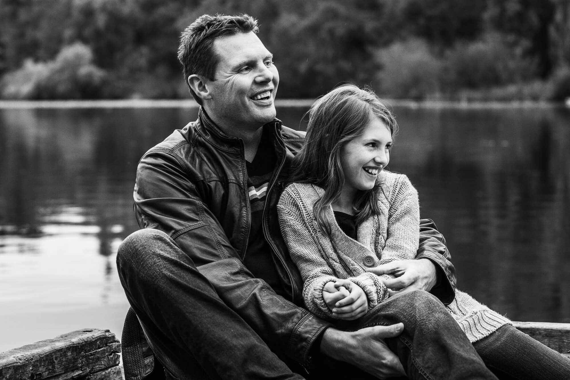 dad and daughter share a laugh next to a lake