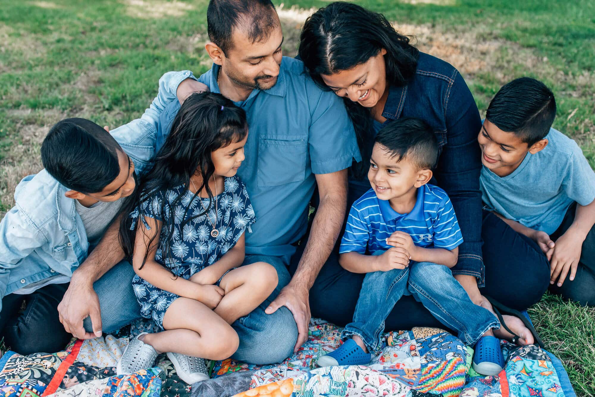 Family with four kids pose on quilt in Coquitlam family photo shoot