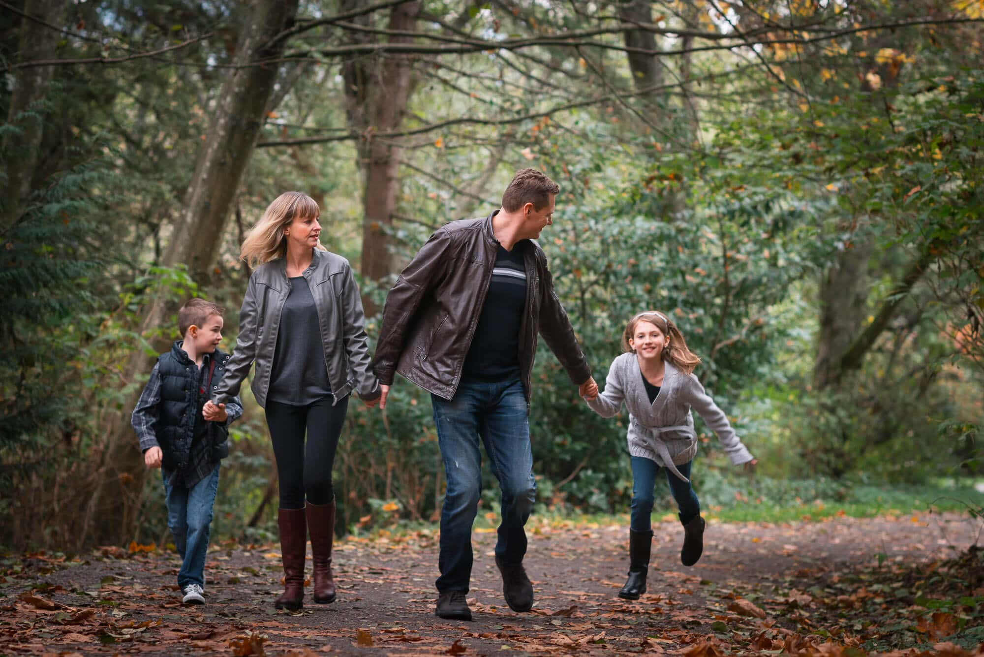 Family running through Deer Lake Park in Burnaby during family photo session