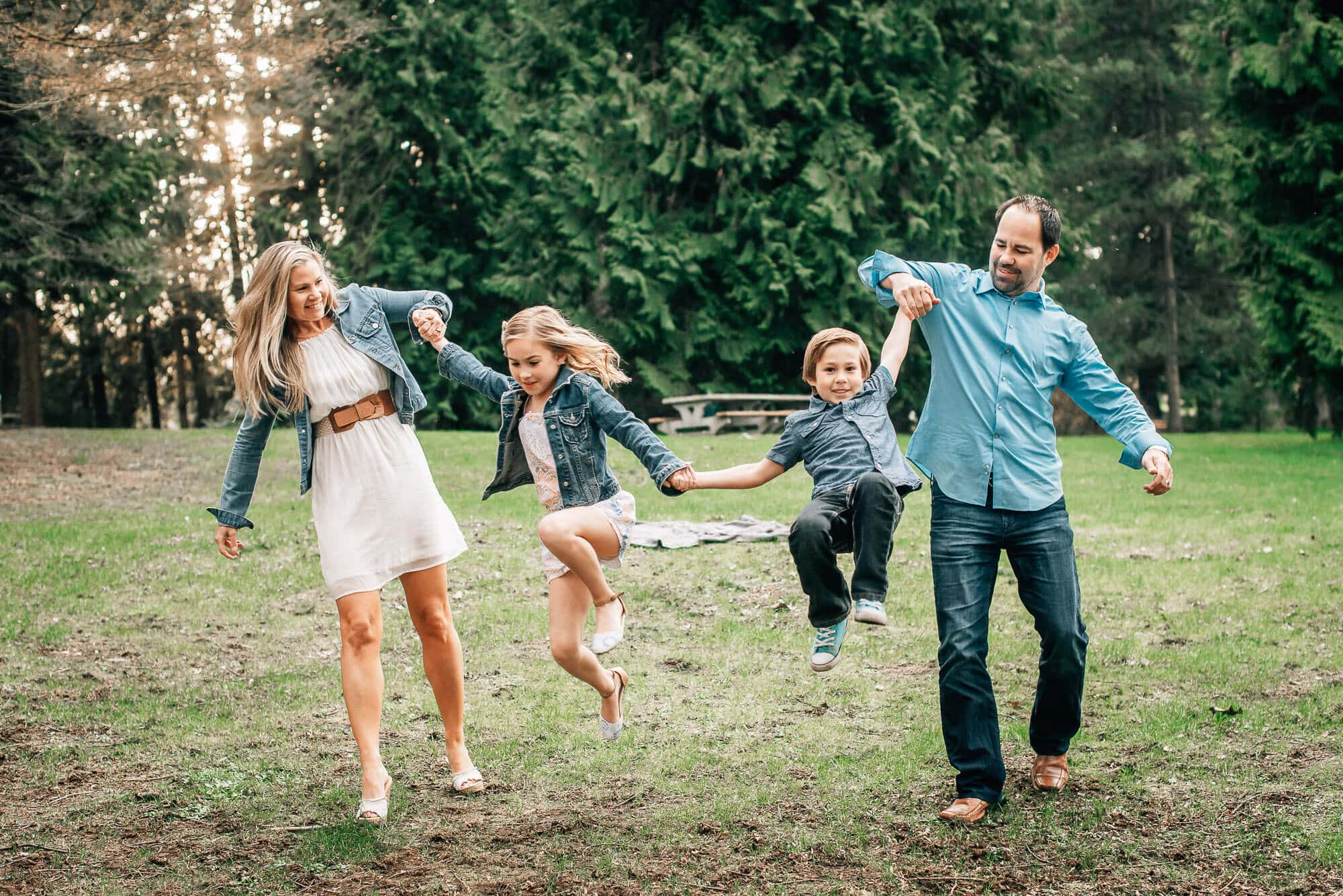 Fun family photography session in park with parents swinging 2 kids between them
