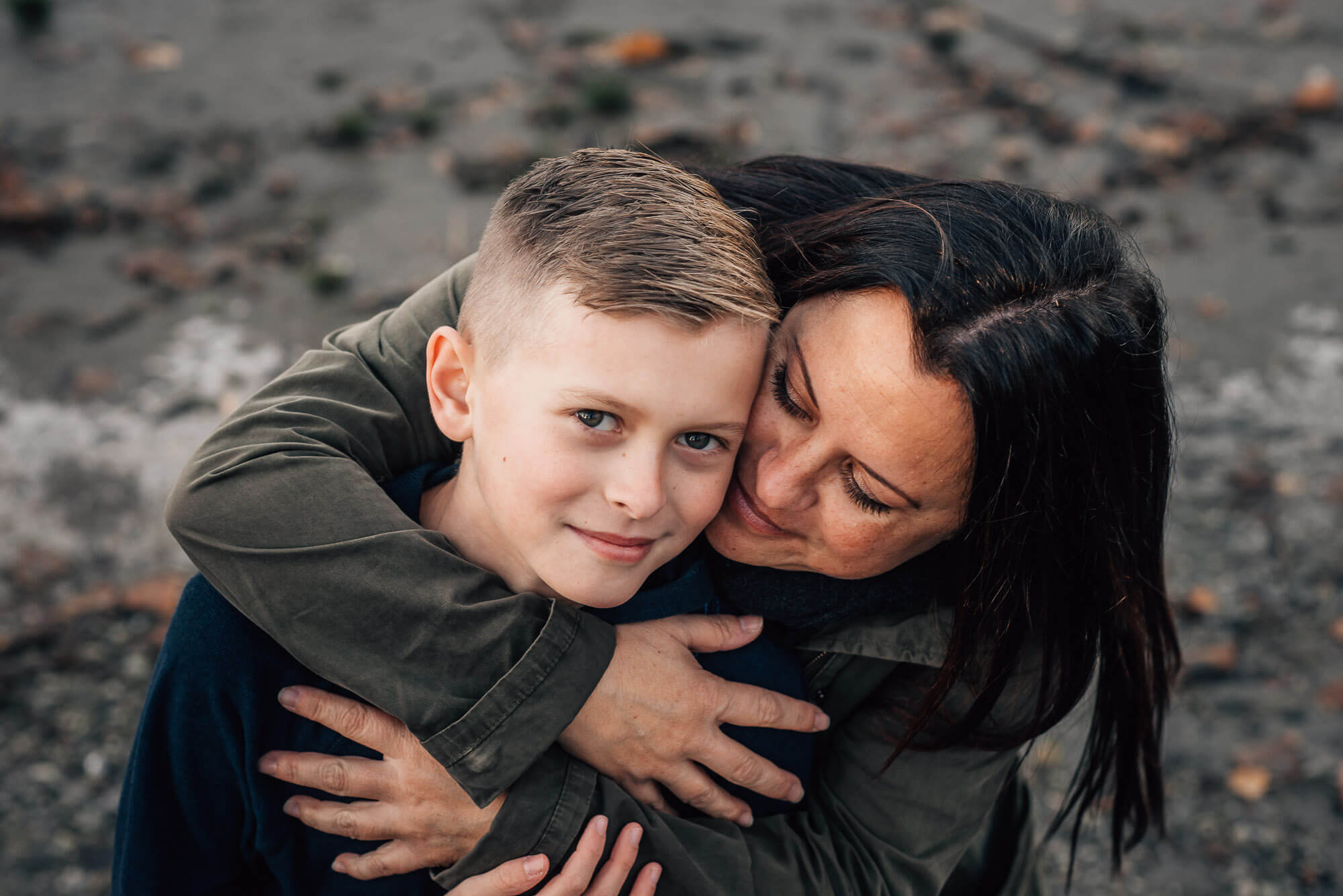 outdoor lifestlye family photos of mom hugging son from behind
