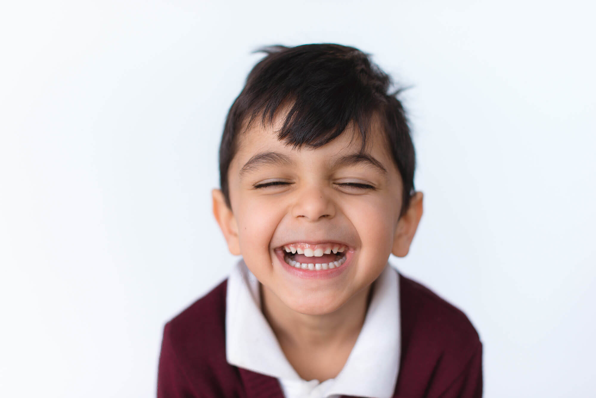 boutique school photography boy with eyes closed and huge grin