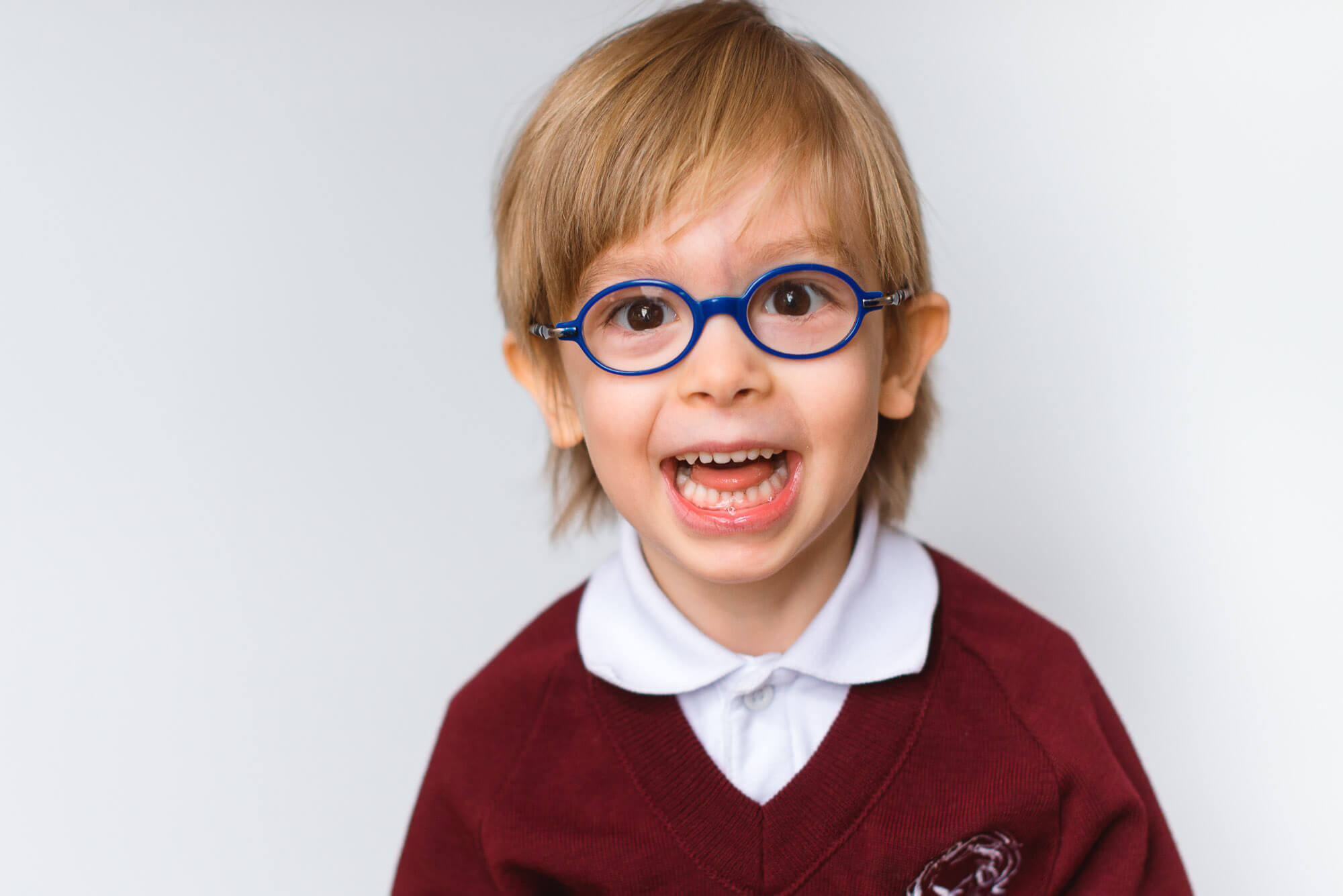 boutique school photography boy with blue glasses and big grin