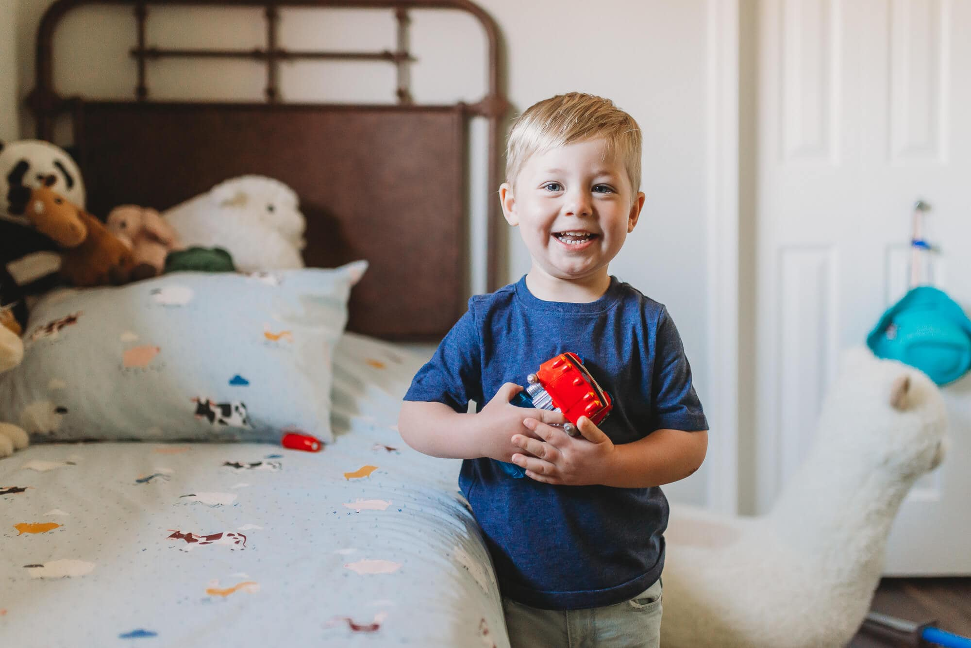 boy standing next to bed with toy car in hand