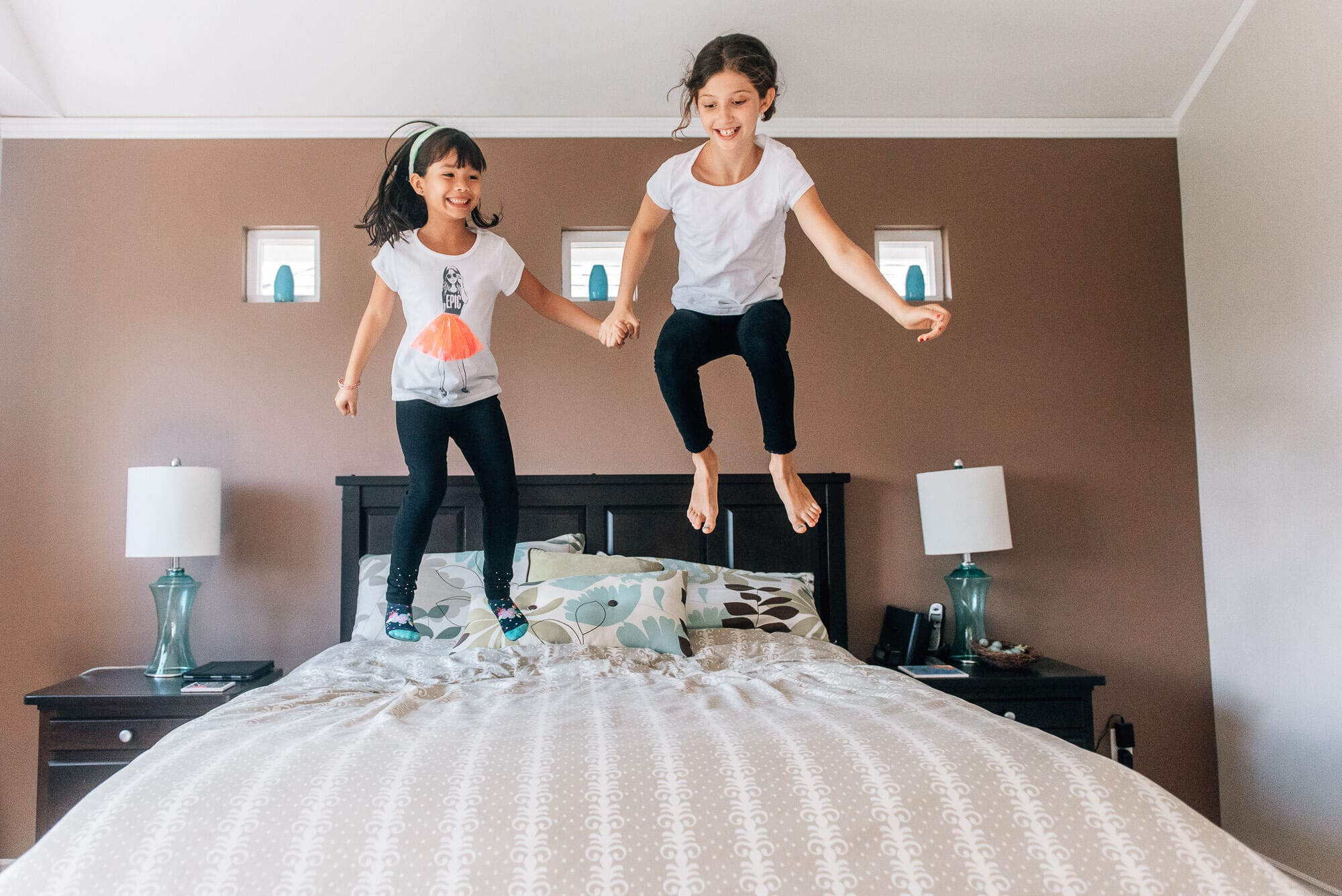 two girls jumping high on a bed