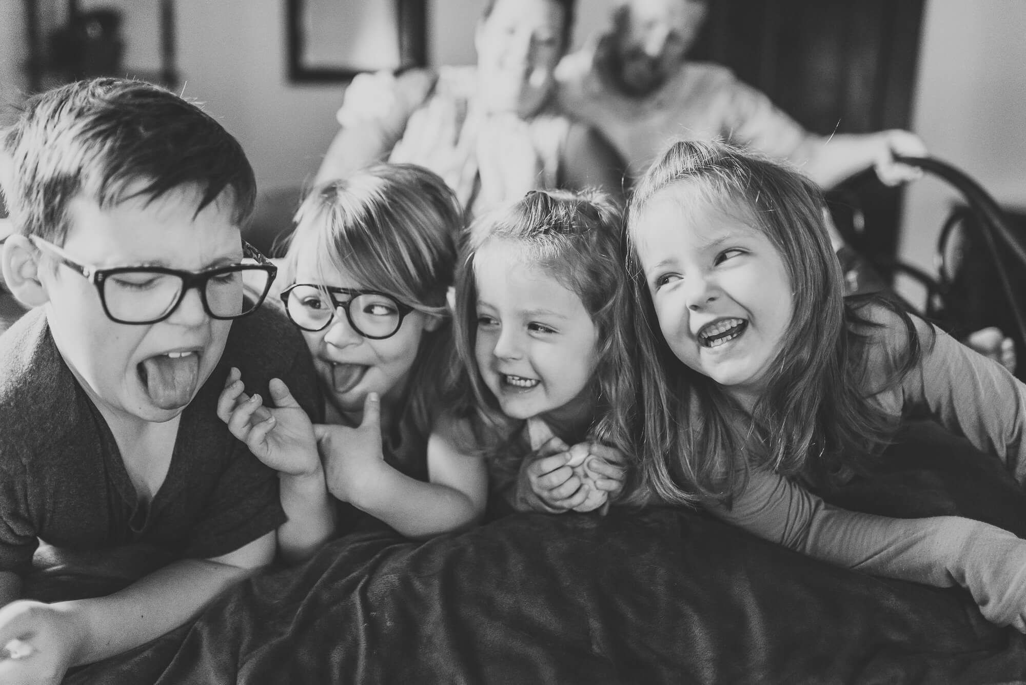 4 siblings lying side by side on bed