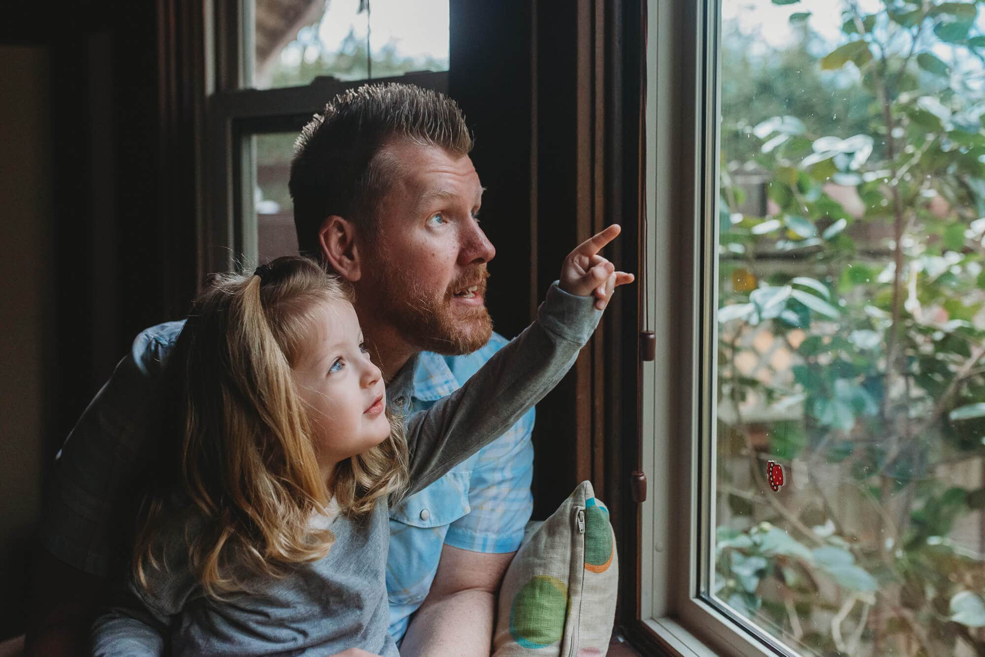 dad and daughter with Vancouver Family Photographer looking out a bay window