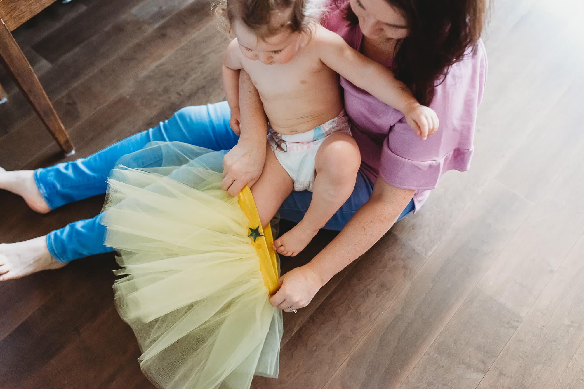 mom helping to put on toddler's yellow tutu