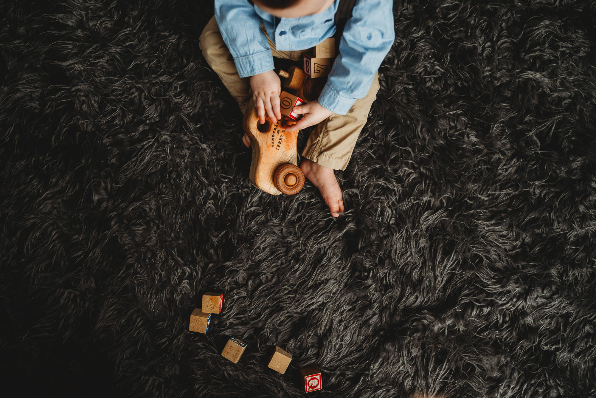 overhead image of boy playing withwooden car and blocks on grey shaggy carpet