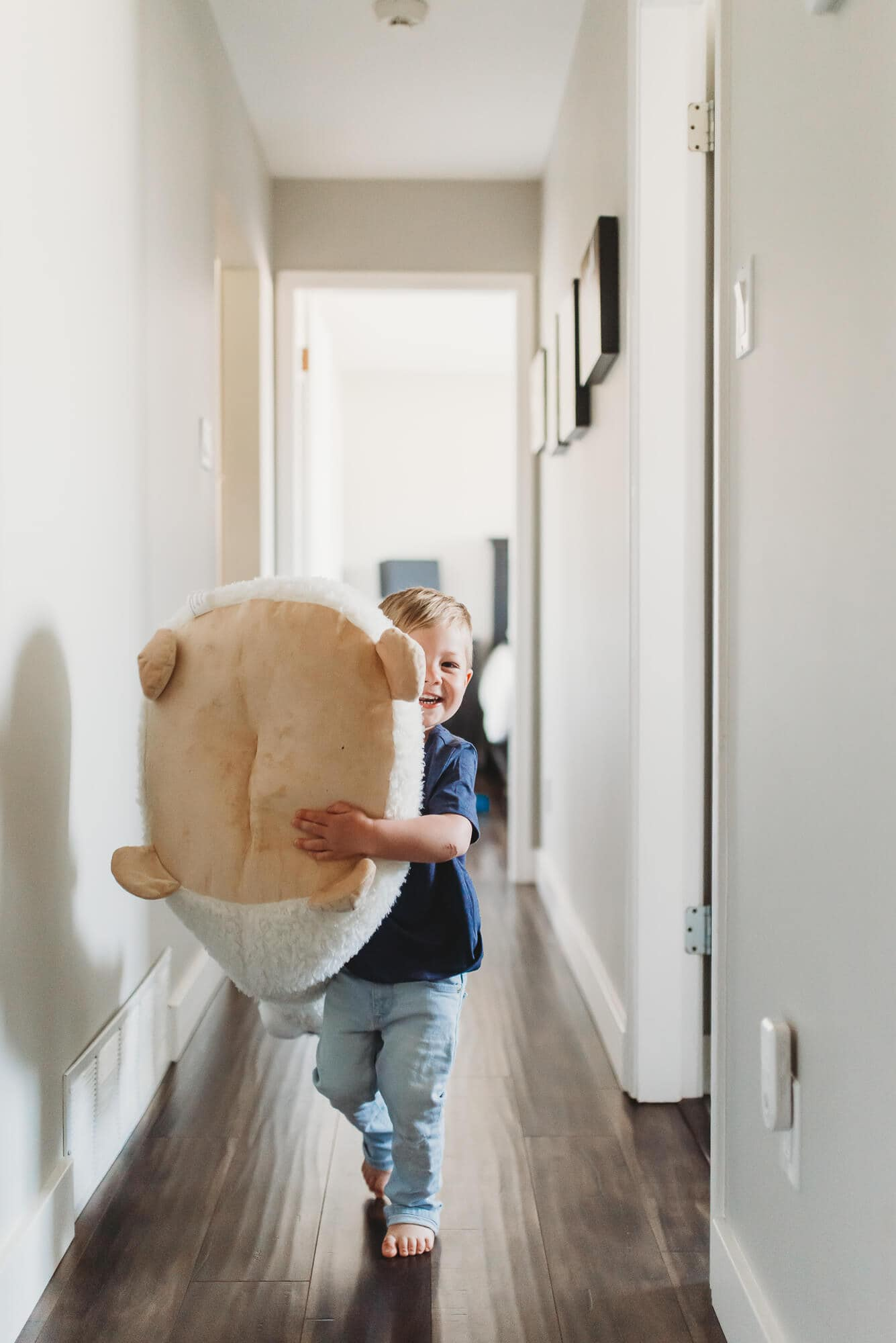 boy running down hall with giant stuffed animal