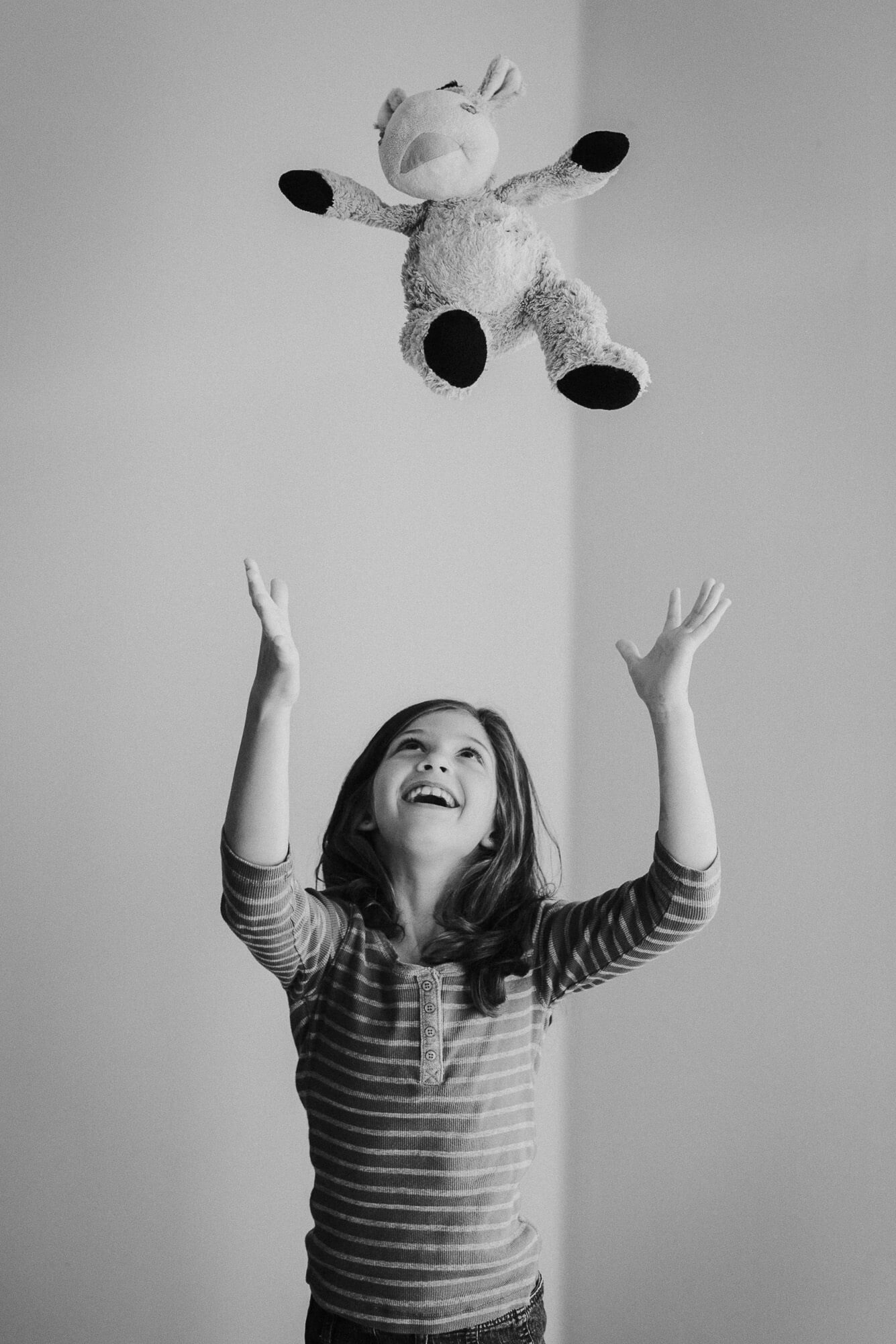 girl throwing stuffed animal up in the air