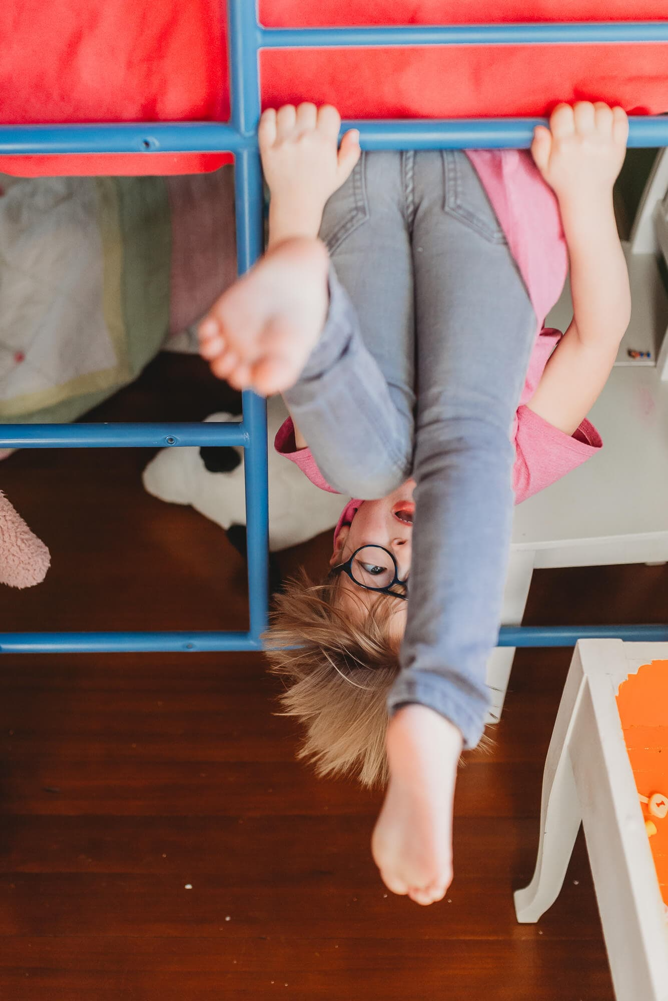 girl hangs upside down from bunk bed during lifestyle session