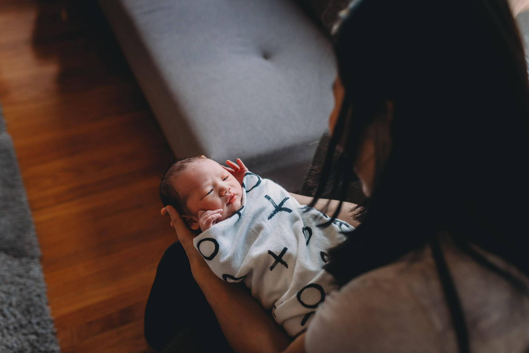 lifestyle Vancouver newborn photographer captures newborn baby looking up at mom