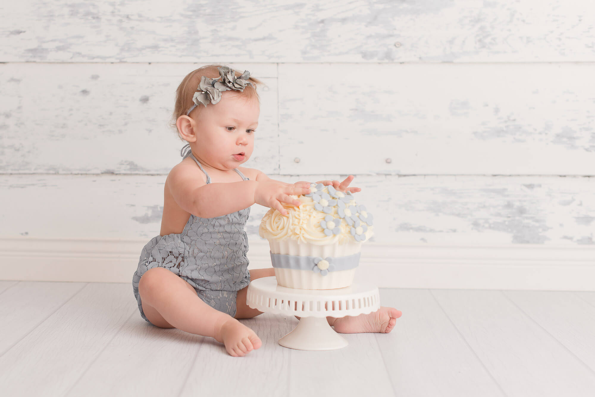 vancouver cake smash photographer captures girl touching flower cake