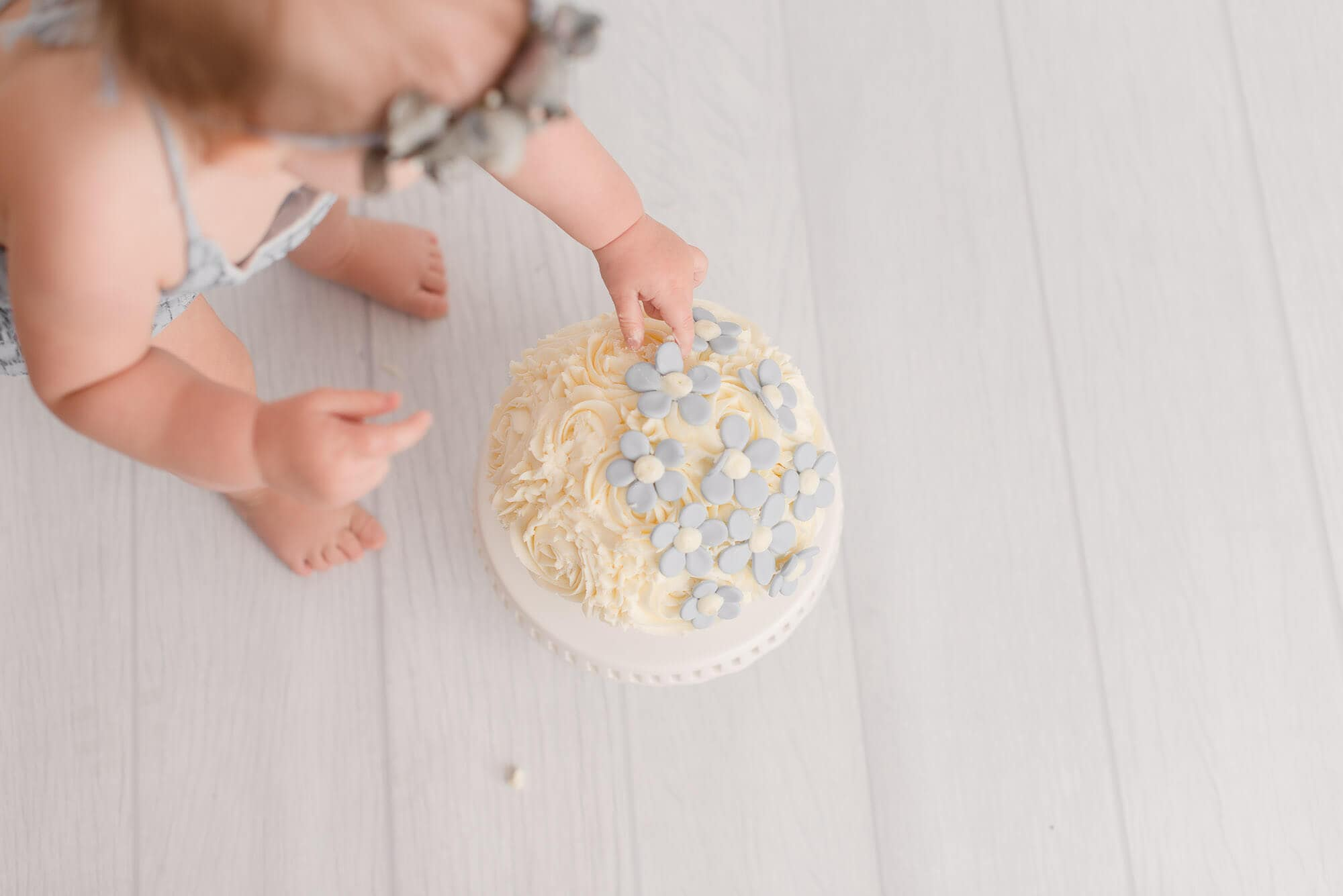 overhead shot of cake smash with grey flowers
