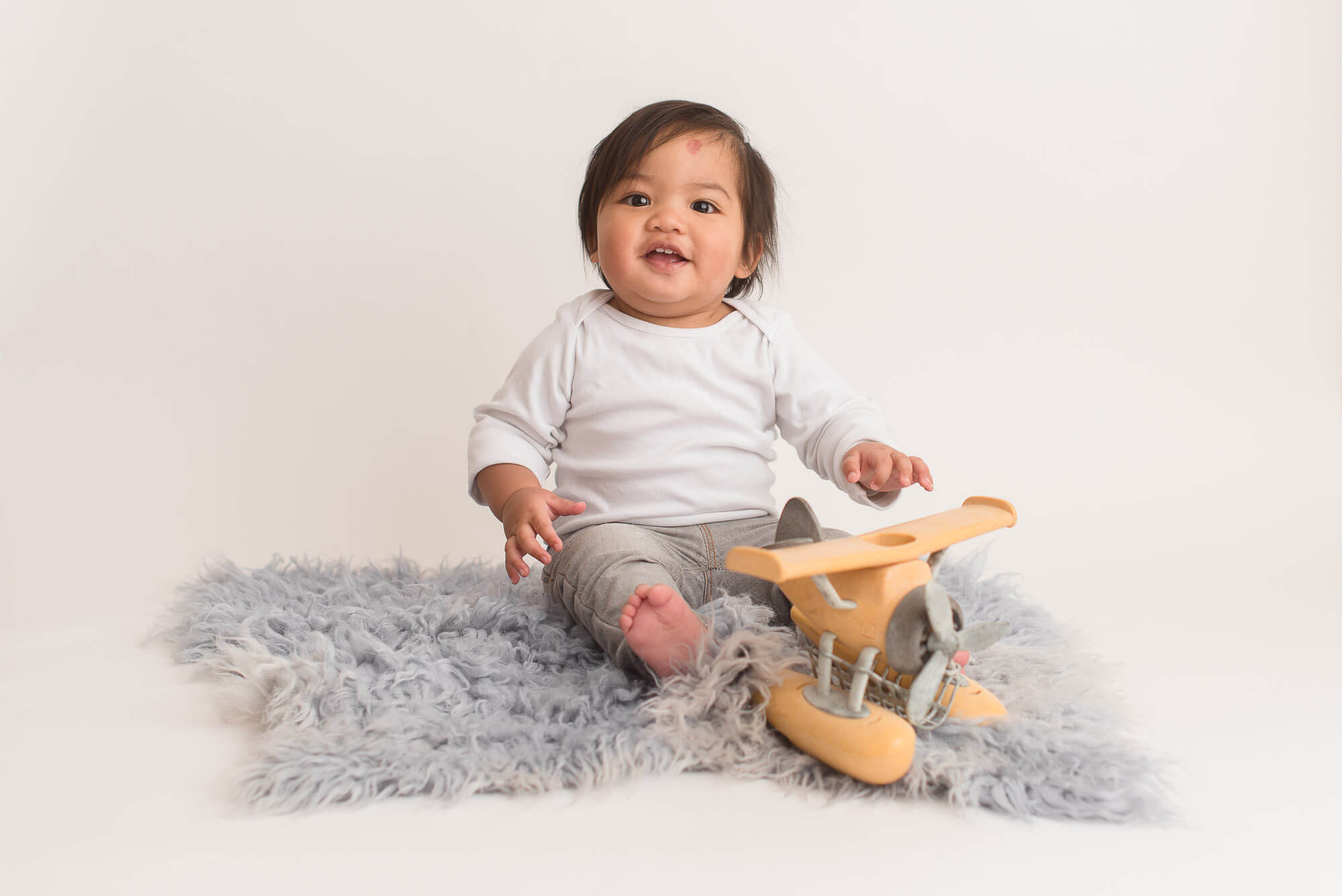 classic and timeless child portrait on fluffy rug with toy airplane