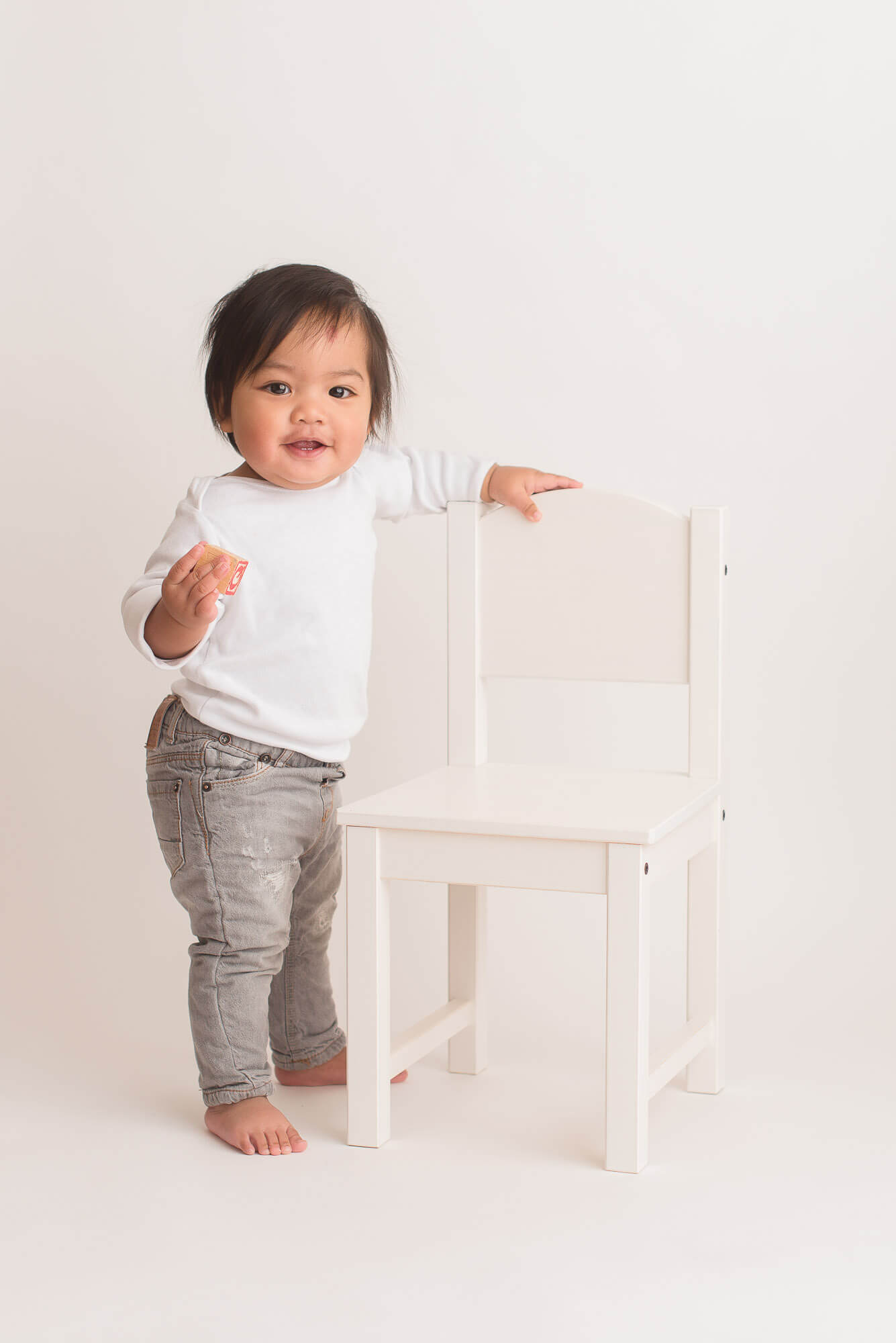 simple child photography session with boy standing next to chair