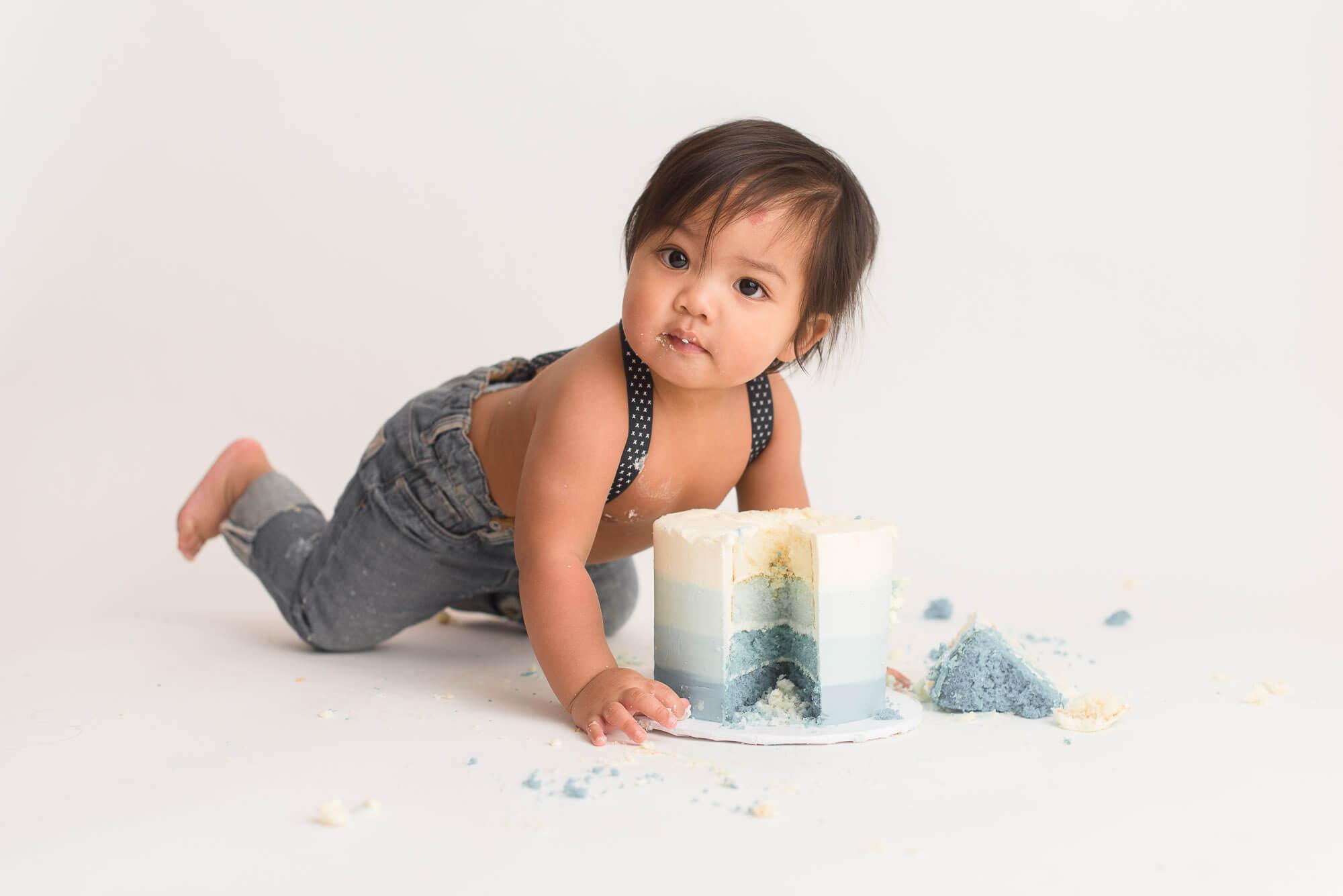 boy crawls towards cake smash cake on simple white background