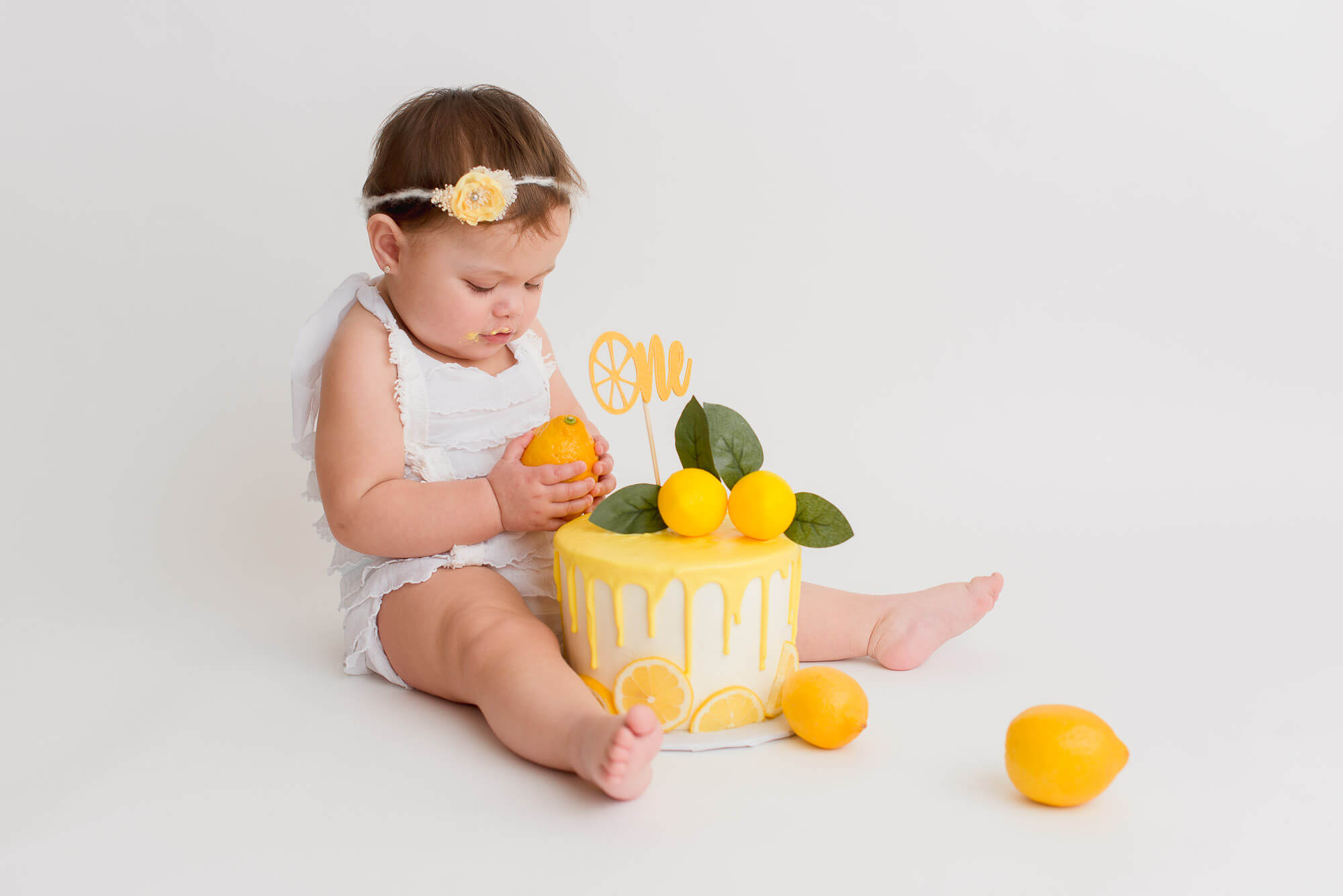 girl sits with lemon cake in her cake smash photography session