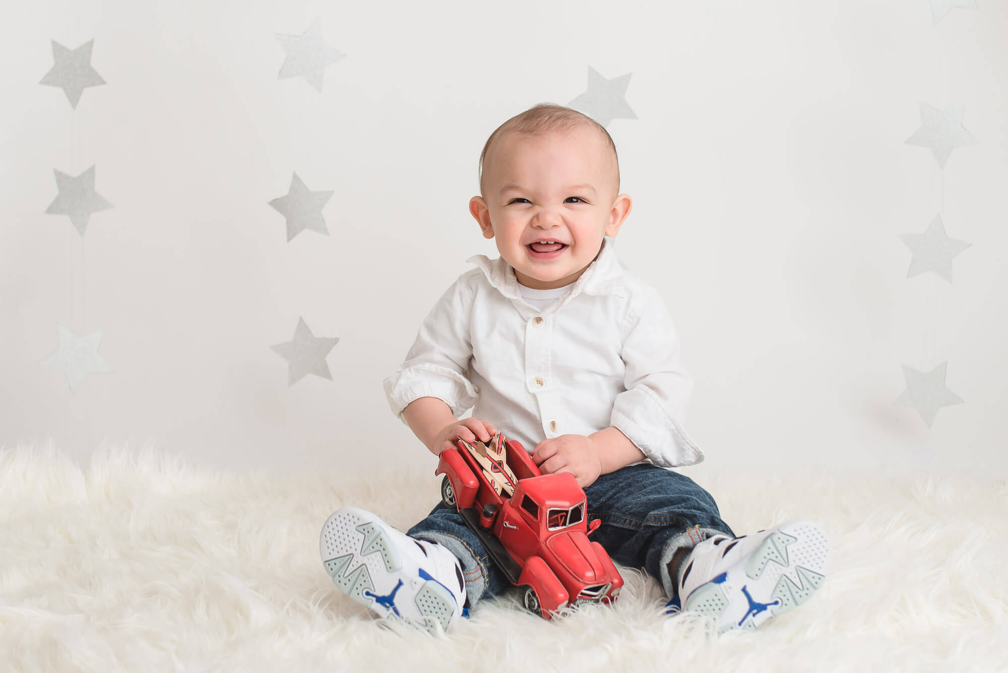 boy sits on fluffy rug with red toy truck during Coquitlam one-year photo session