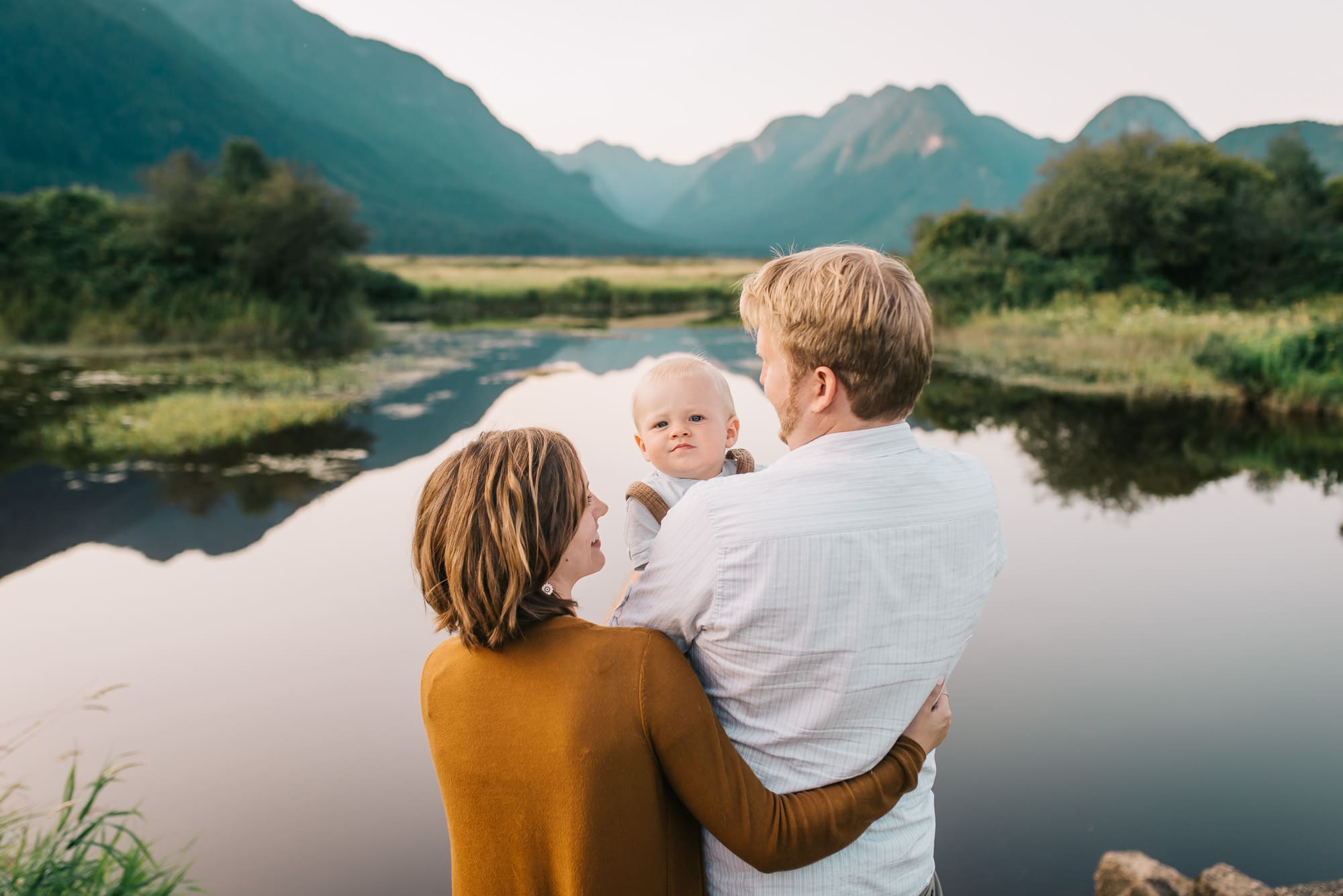 mom dad and baby standing in front of lake and mountains at Pitt Lake