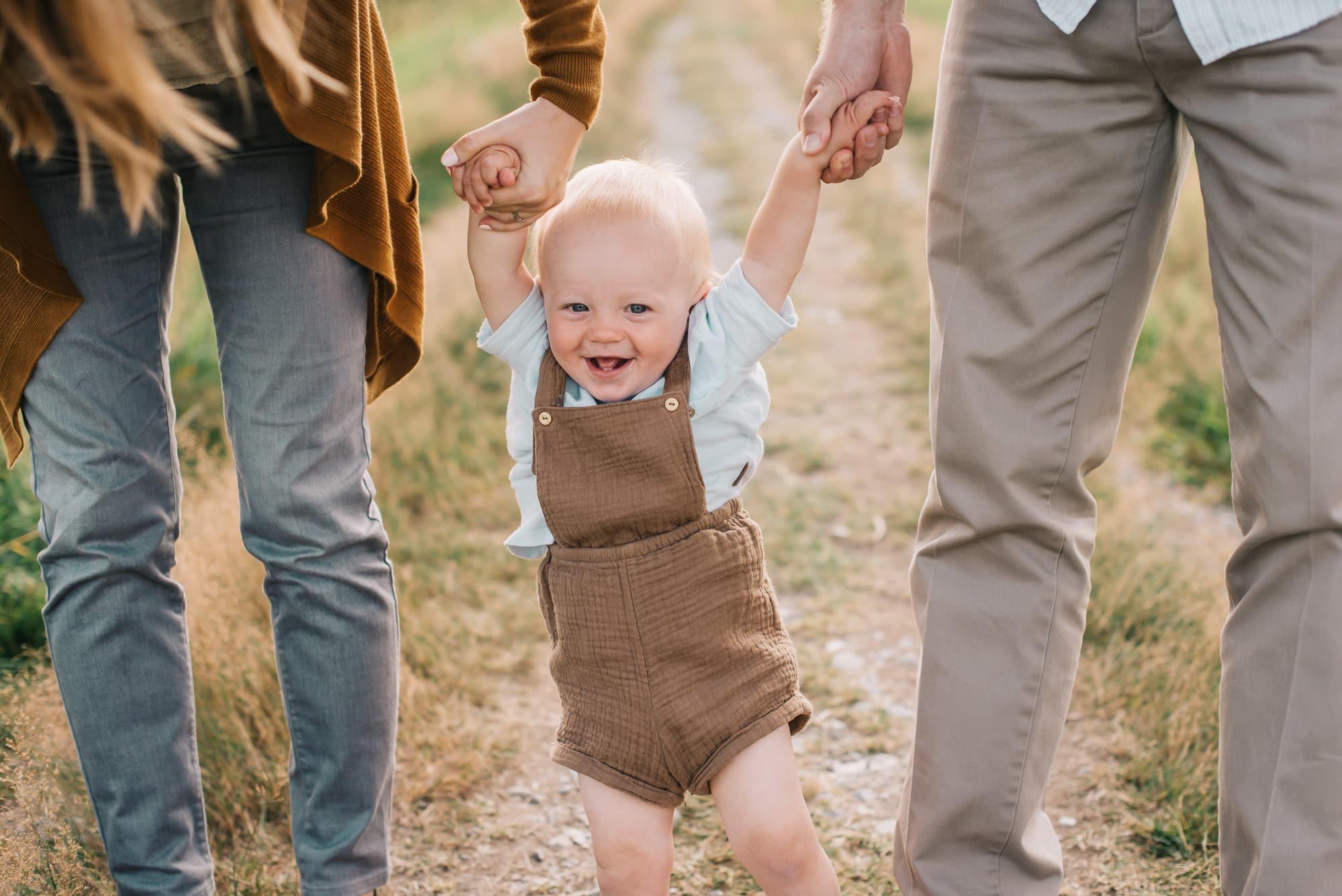 little boy walking between his parents