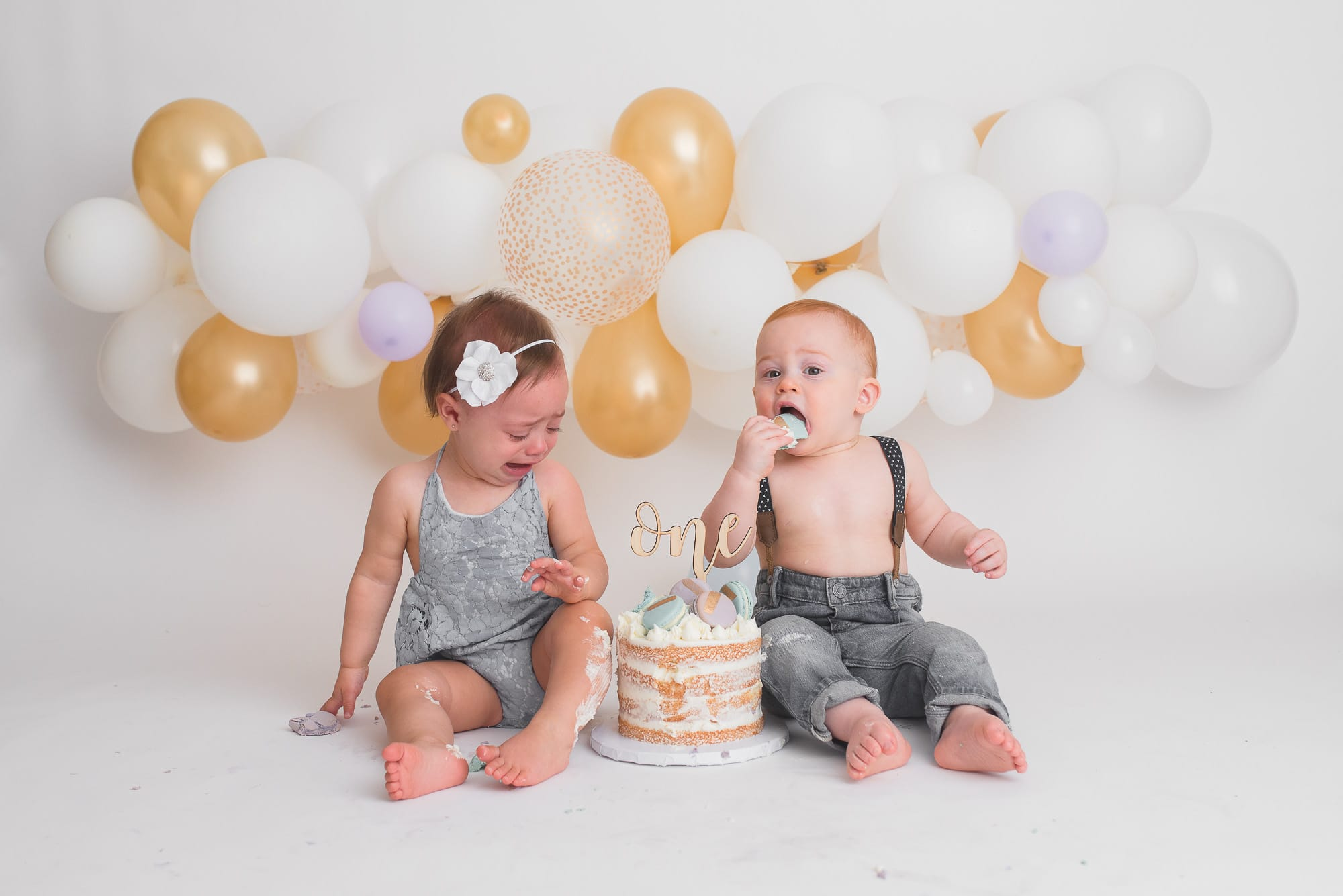 twin cake smash with white and gold balloon garland