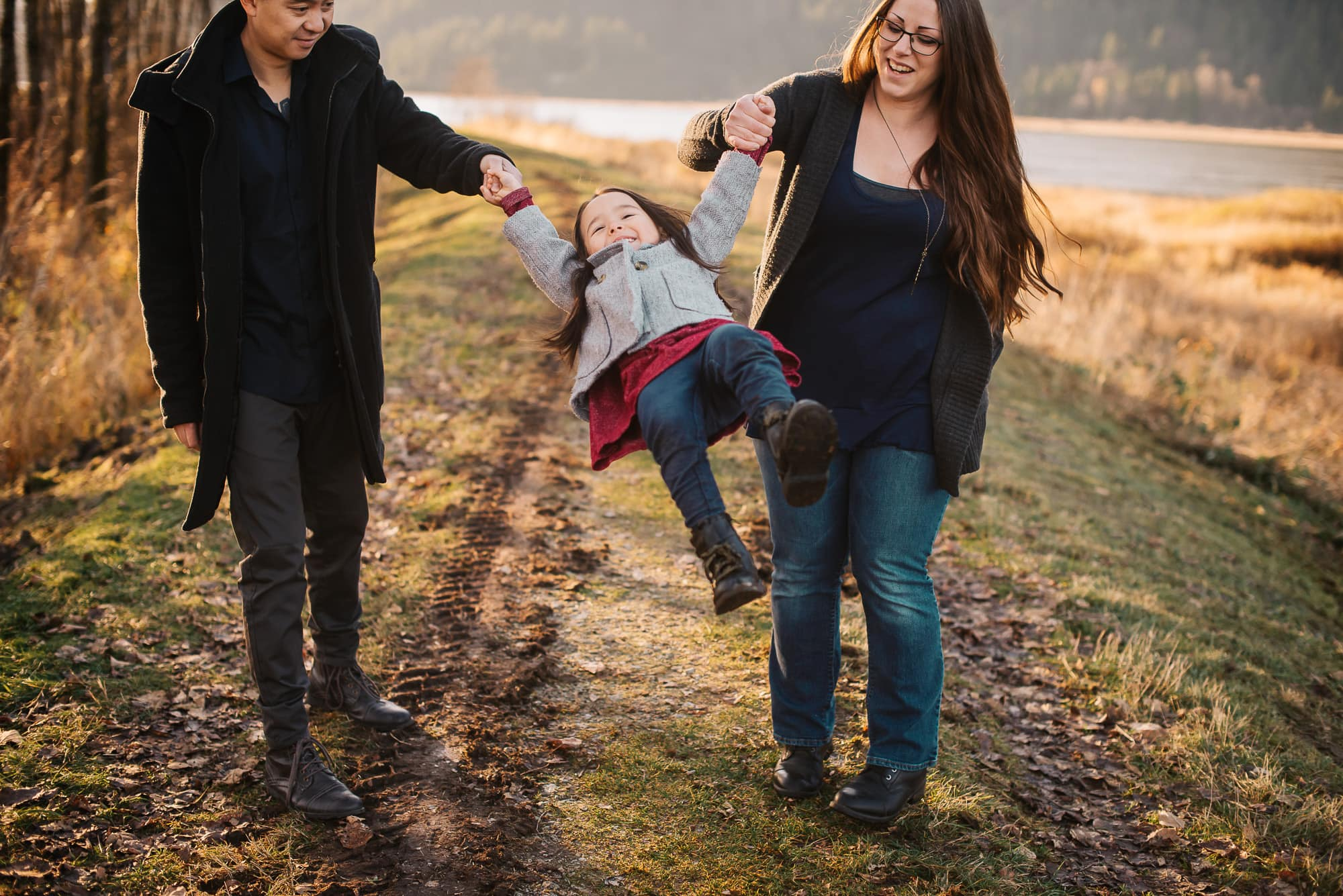 girl swinging between parents in session with Vancouver Family Photographer