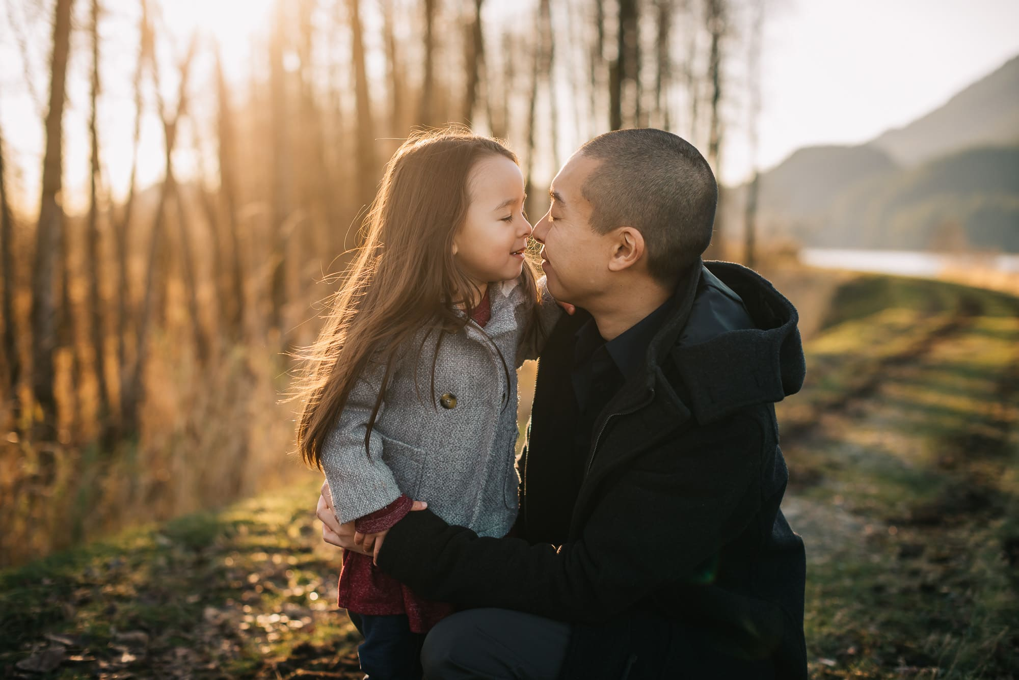 Vancouver Family Photographer shows girl and dad doing nose kisses at sunset