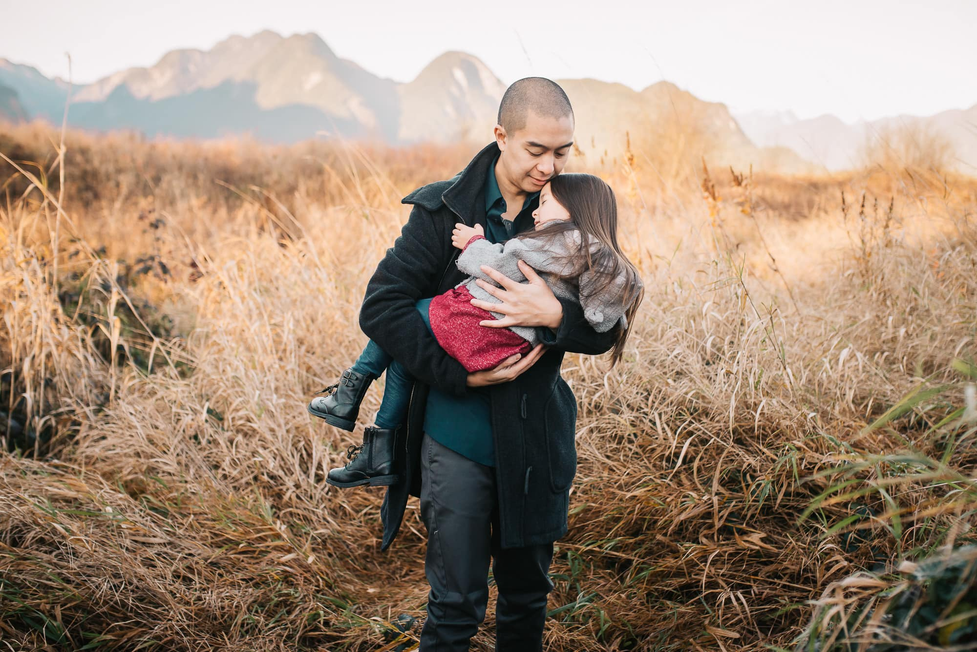 Vancouver Family Photographer captured tender moment of dad carrying daughter through reeds in Pitt Lake