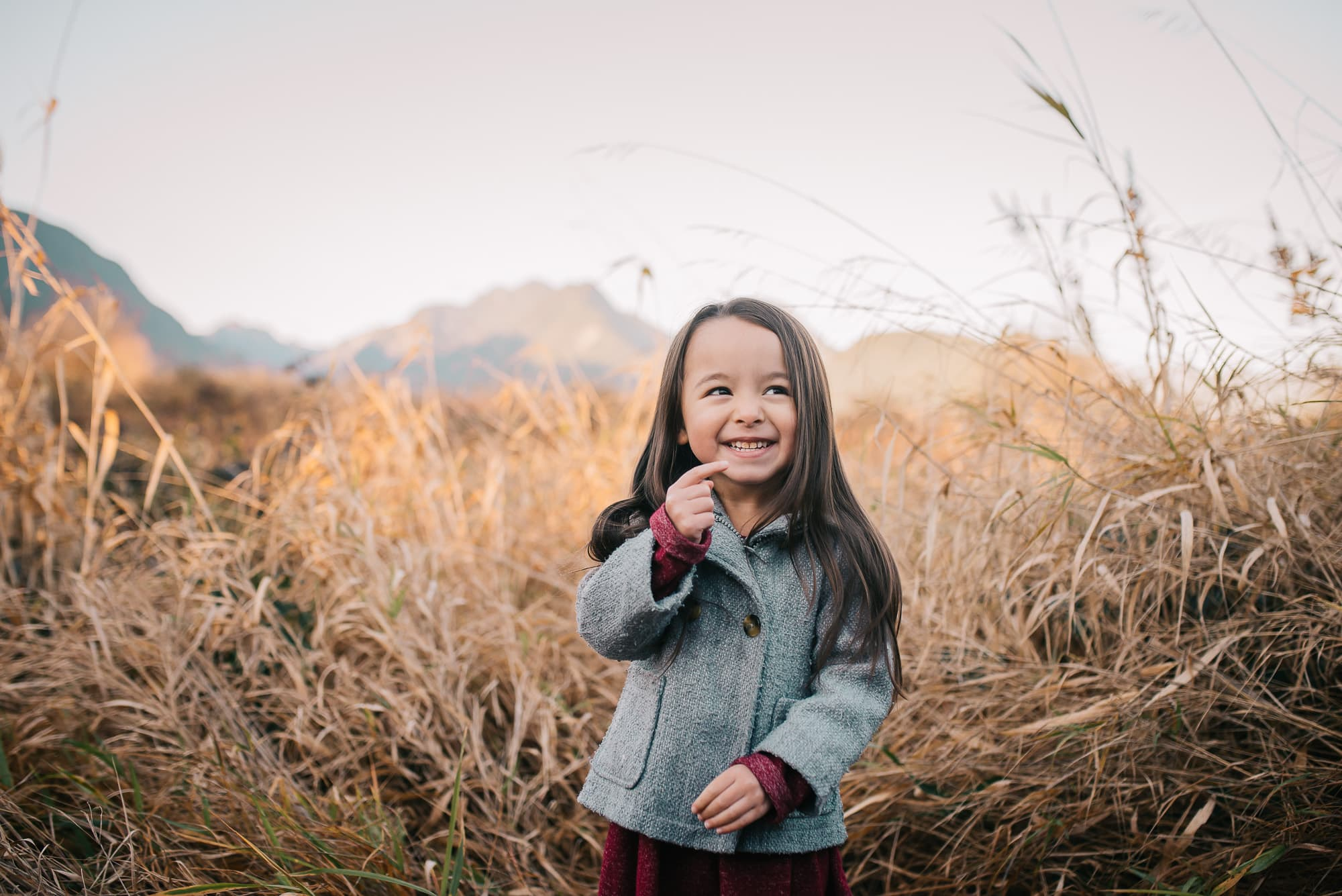 Vancouver Family Photographer makes girl giggle in reeds during family photo session