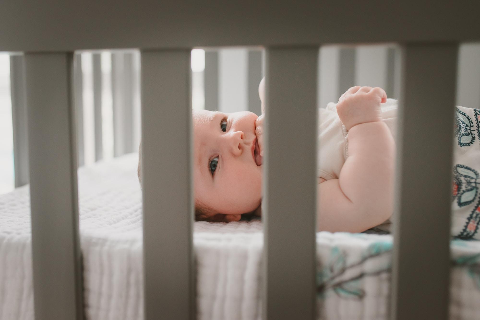 Vancouver Family Photographer captures girl peeking through crib rails