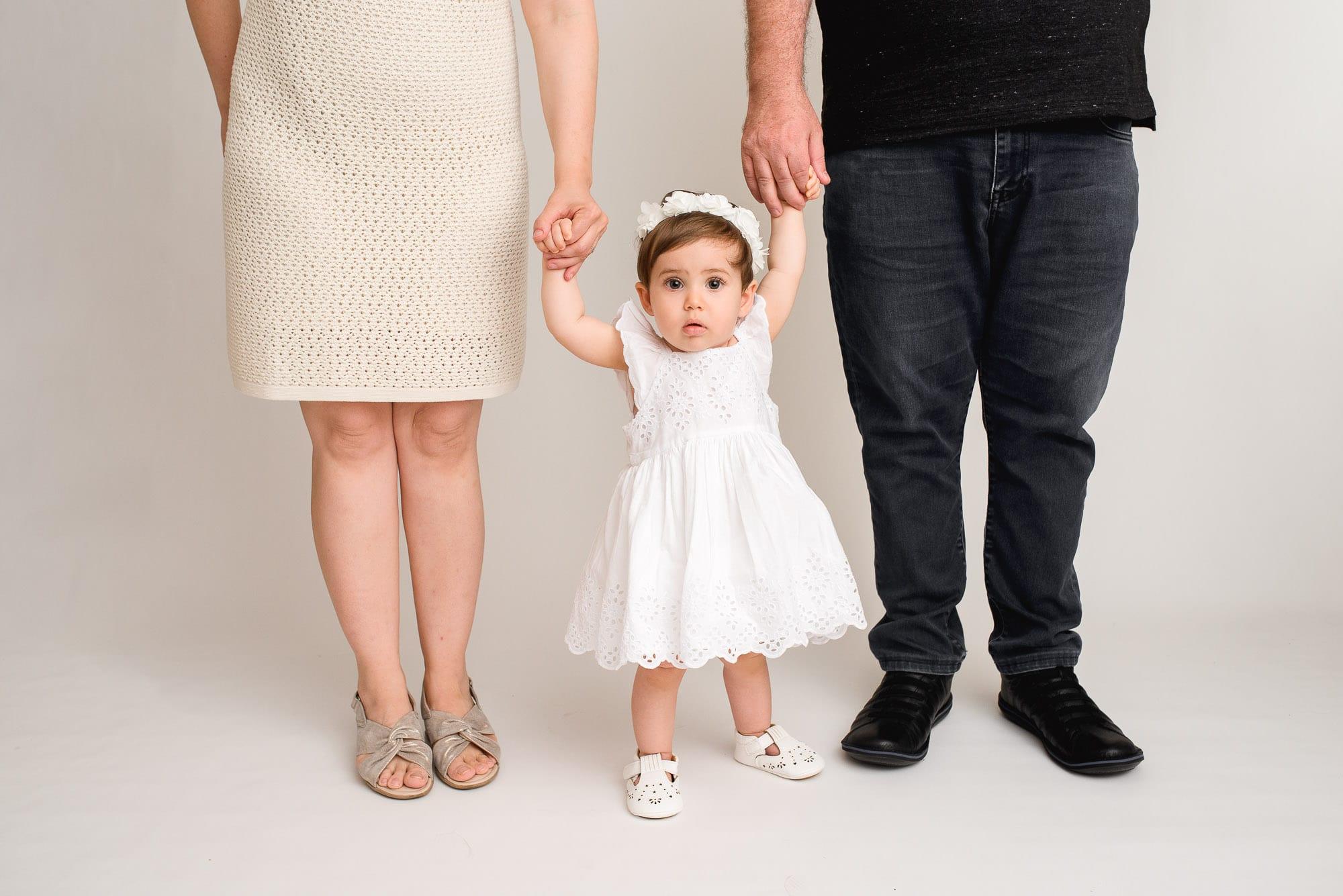 in-studio toddler standing between parents