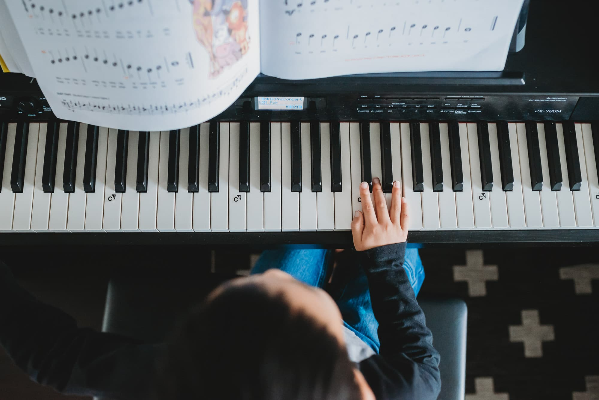 overhead view of boy playing piano