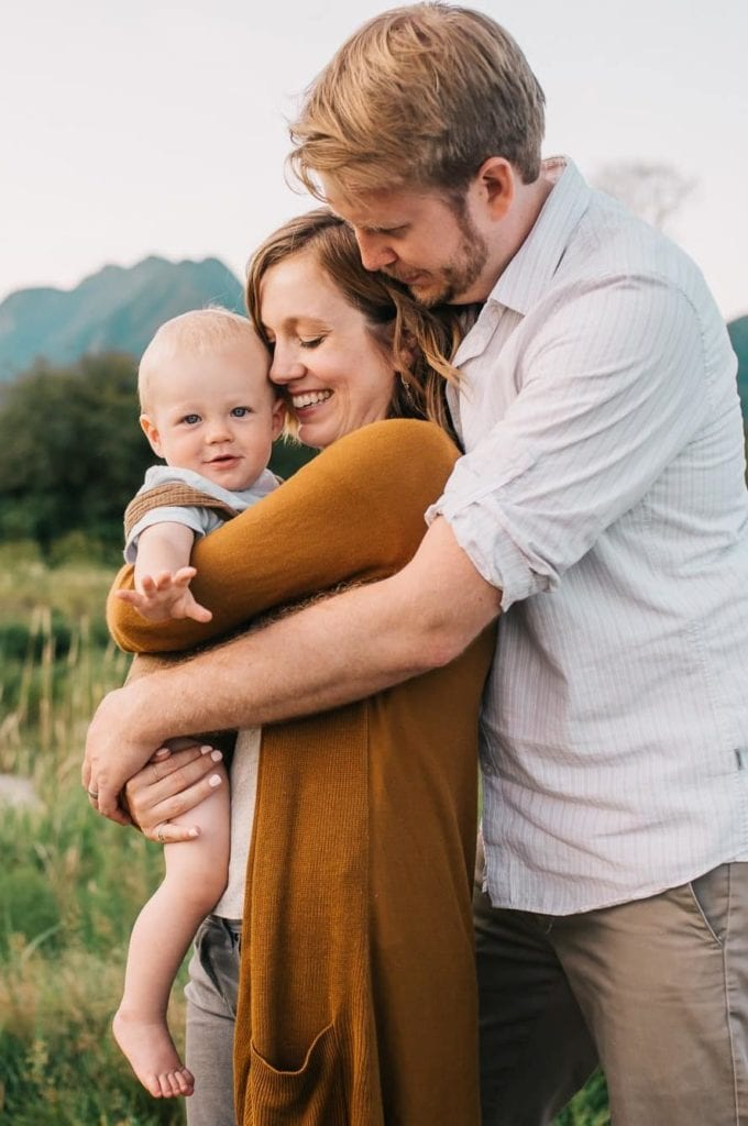 Vancouver family photographer with hugging family with mountains