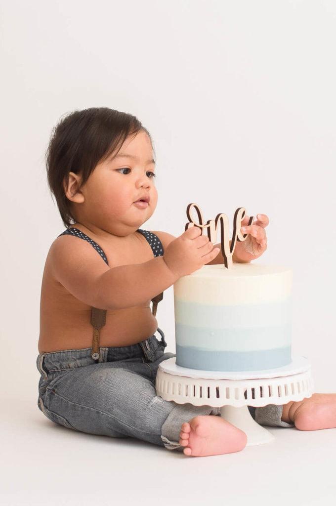 one-year old boy celebrates his cake smash photo session