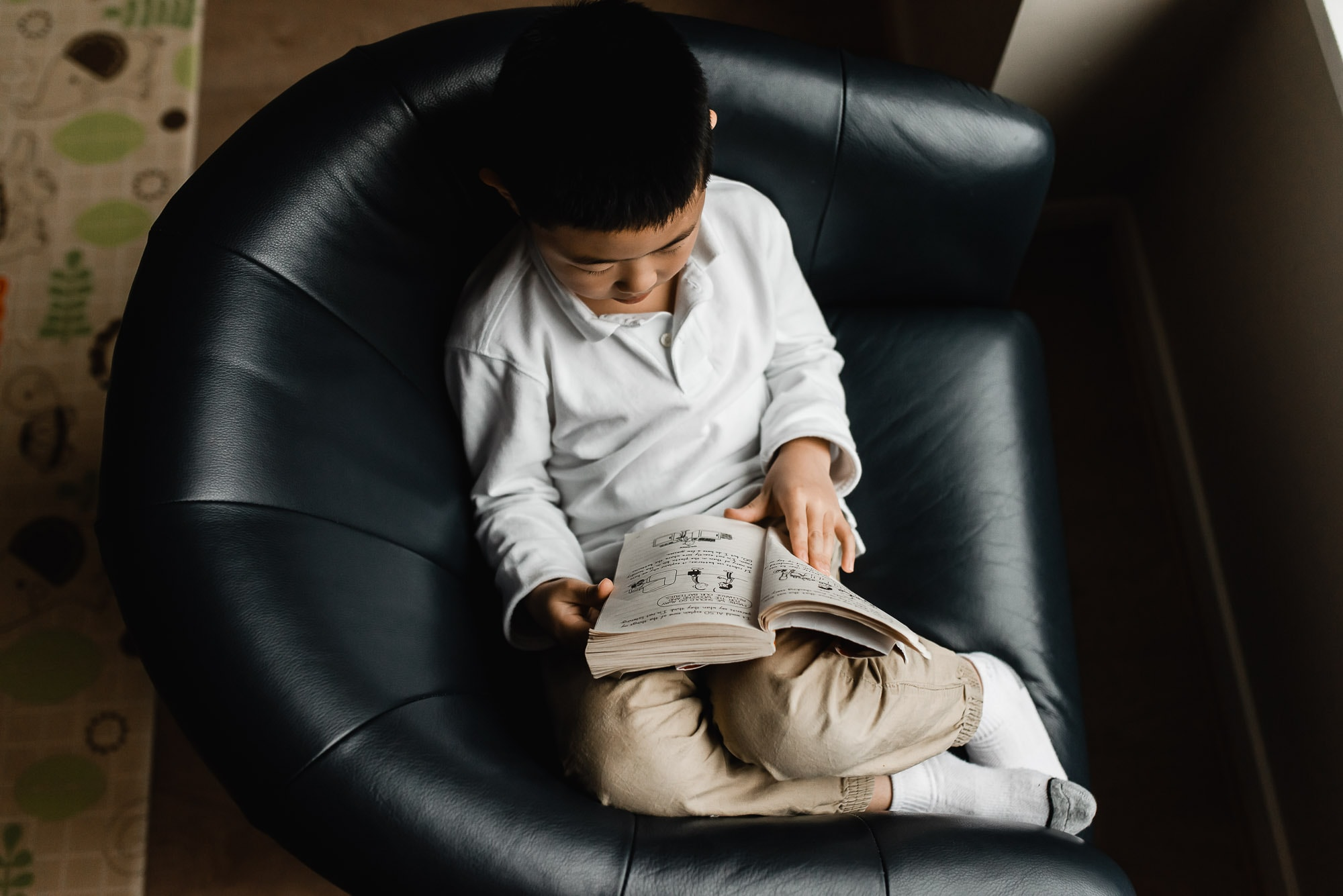 boy reading in chair in Burnaby family photo session