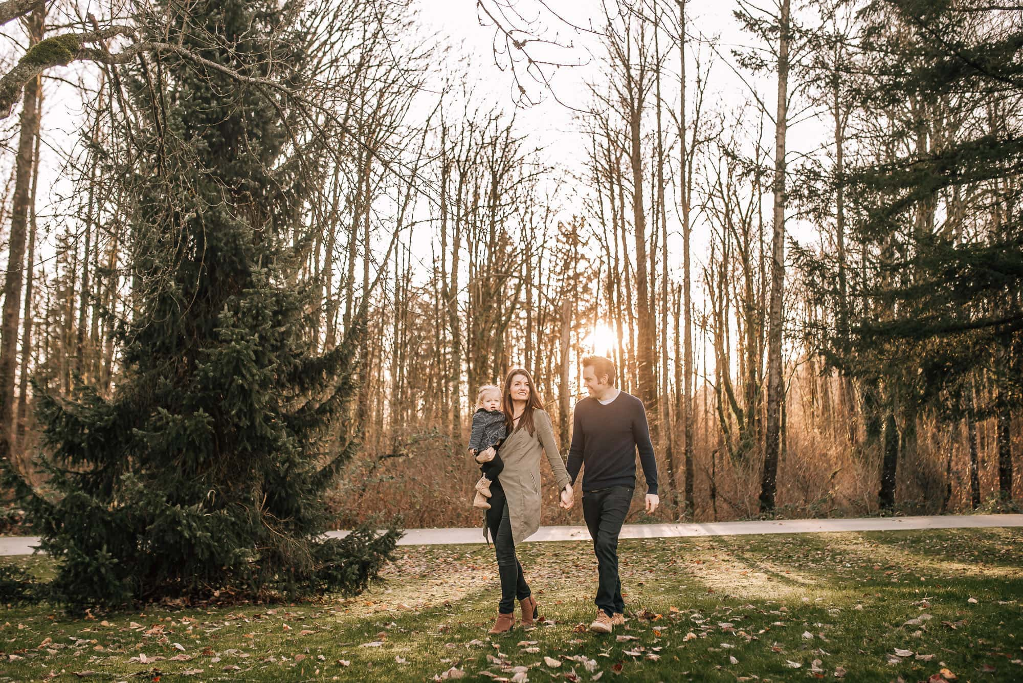 Couple walking with girl in arms as directed by their Vancouver Family Photographer