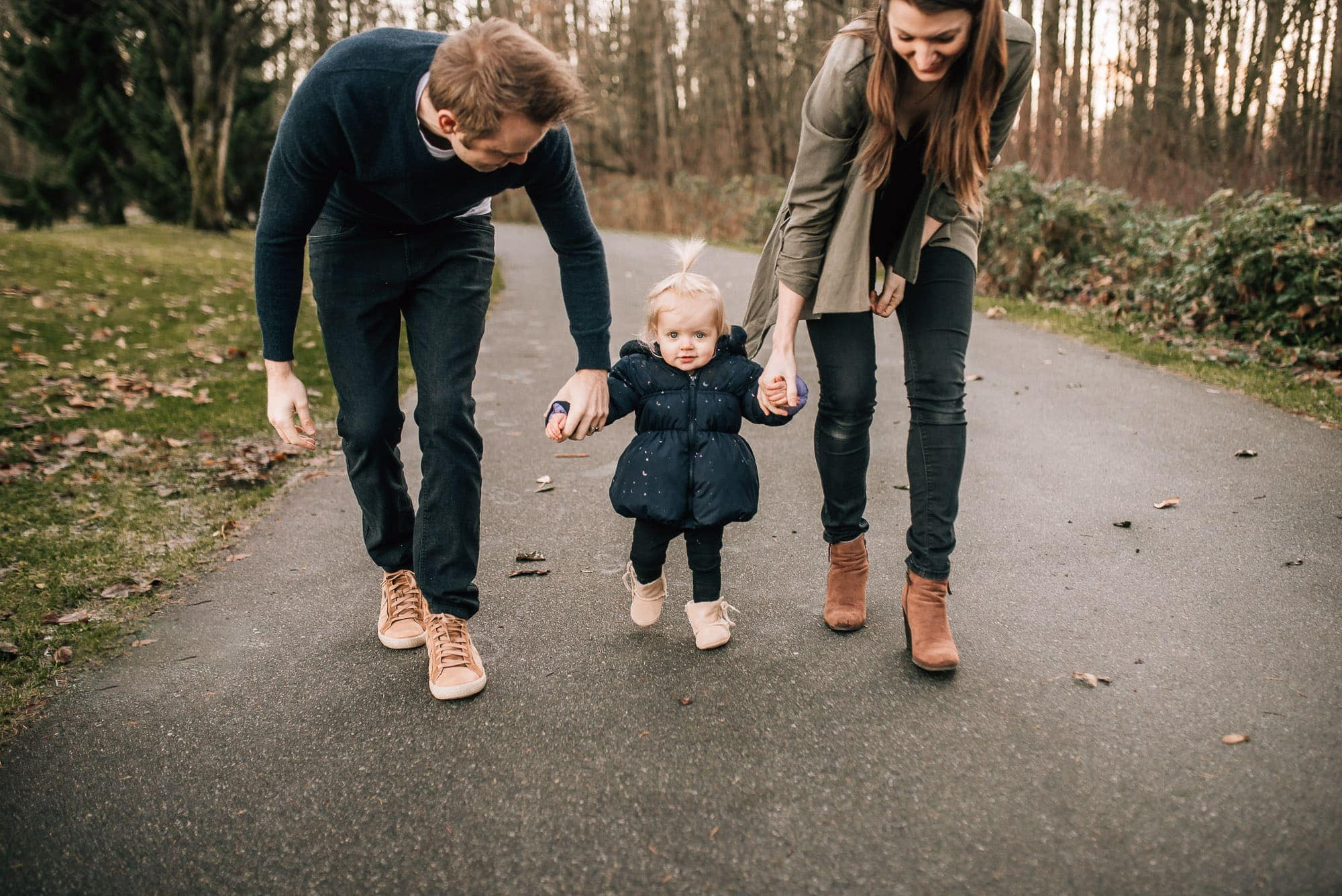 toddler girl walks between parents towards Vancouver Family Photographer