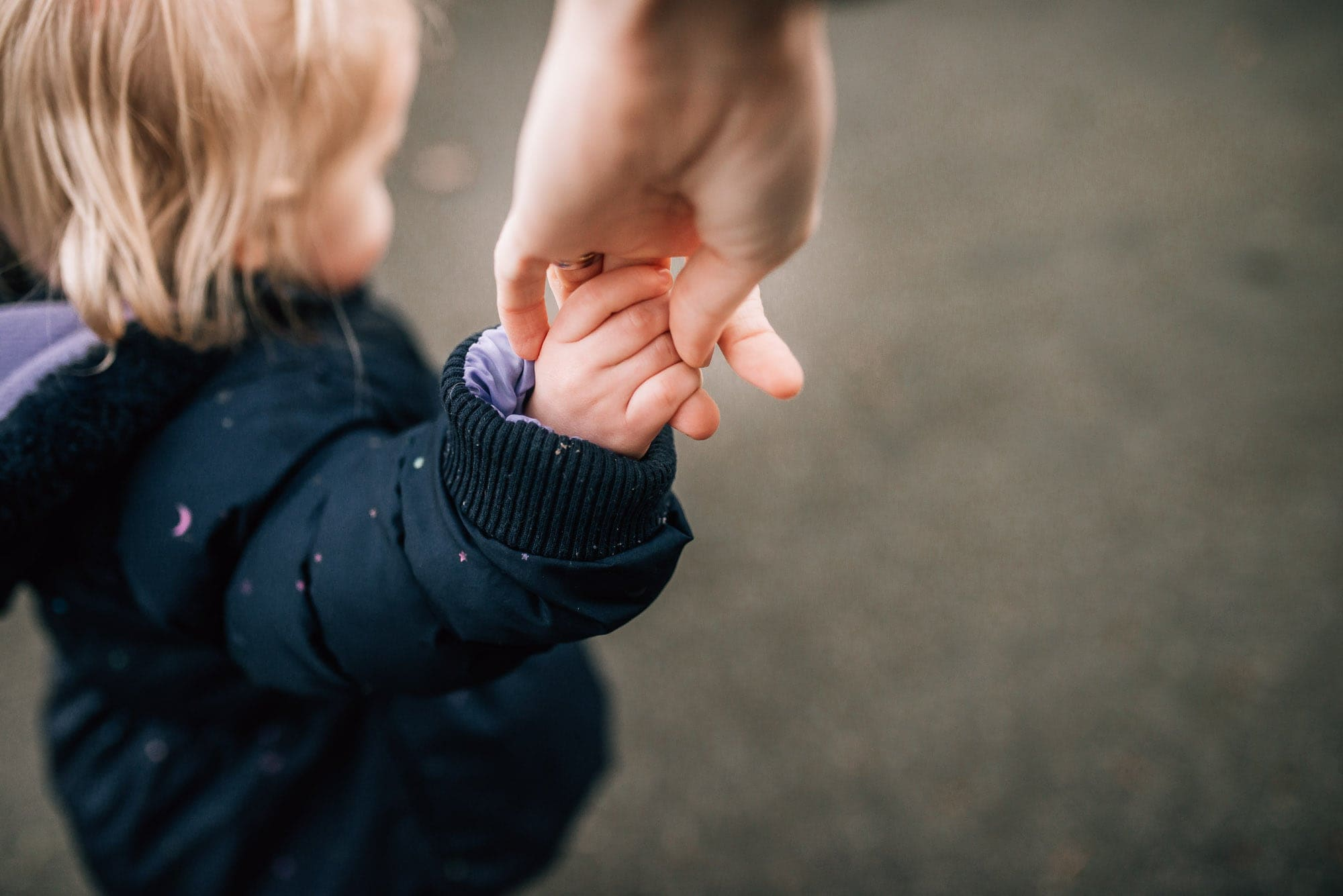 girl holding moms hand from mom perspective