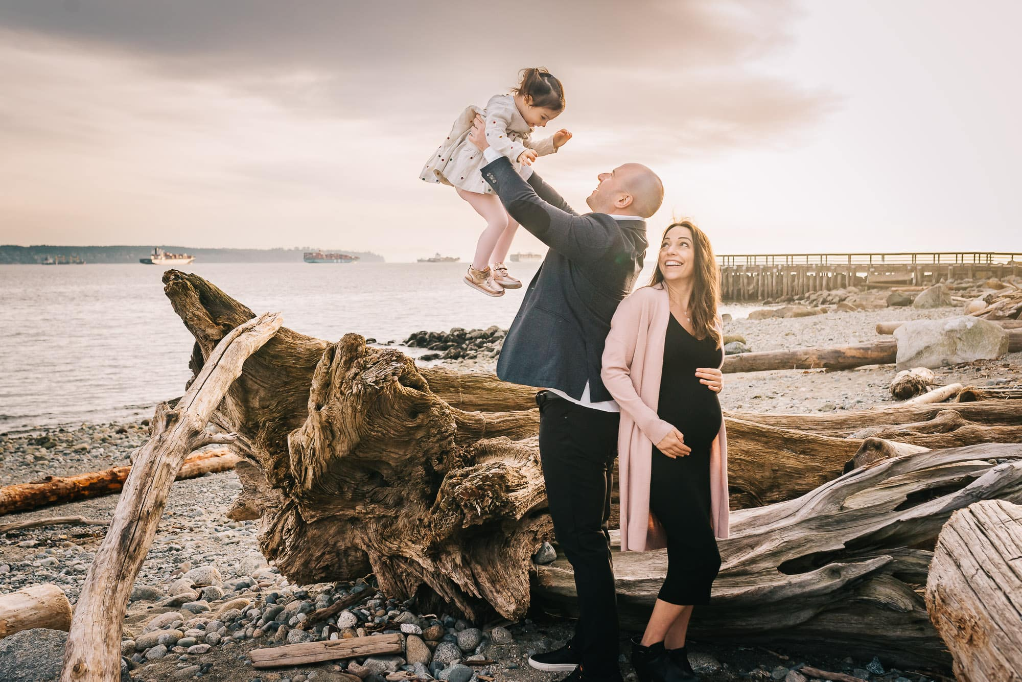 dad lifting girl into air at vancouver beach family session