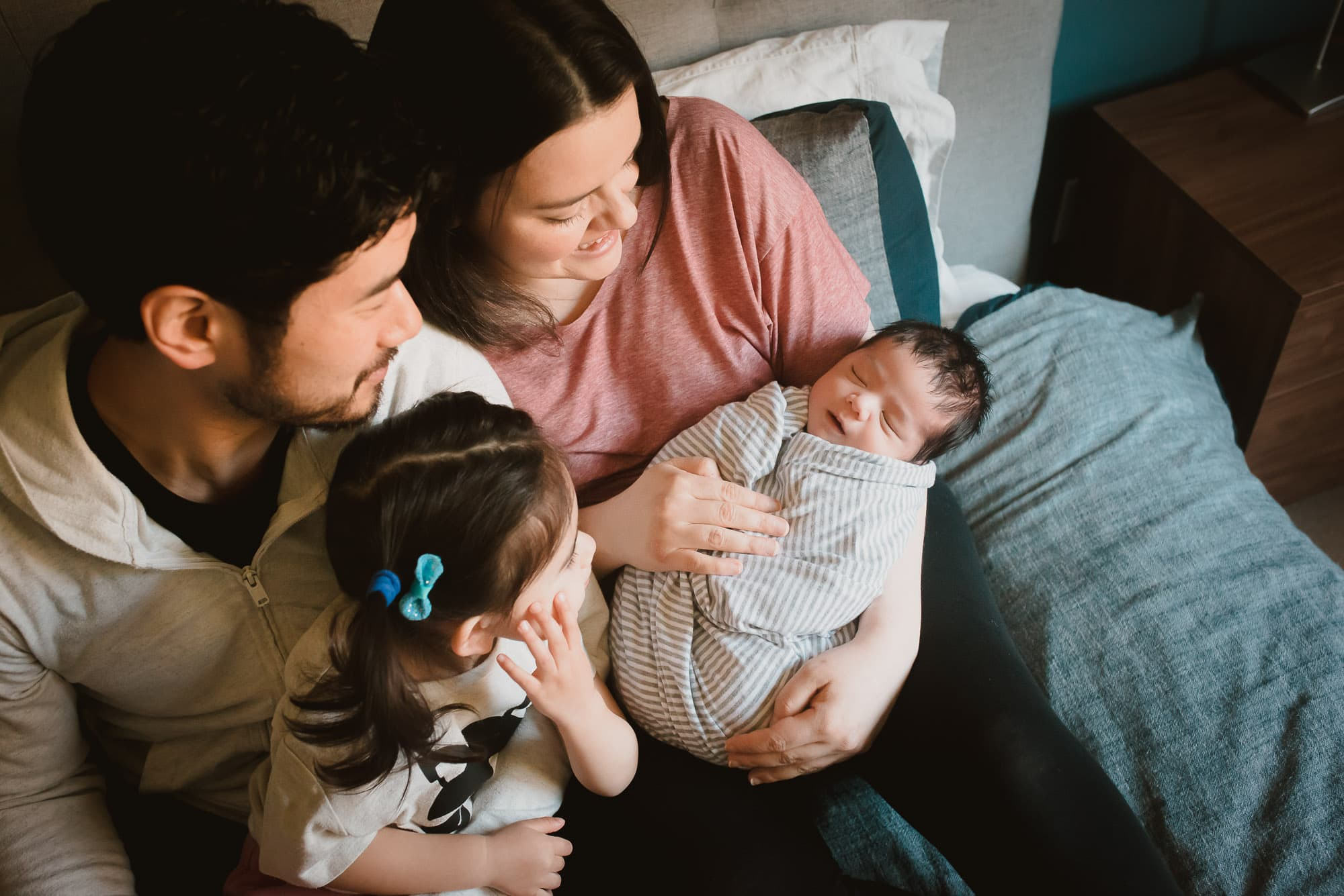 port coquitlam family looks at newborn baby during photo shoot
