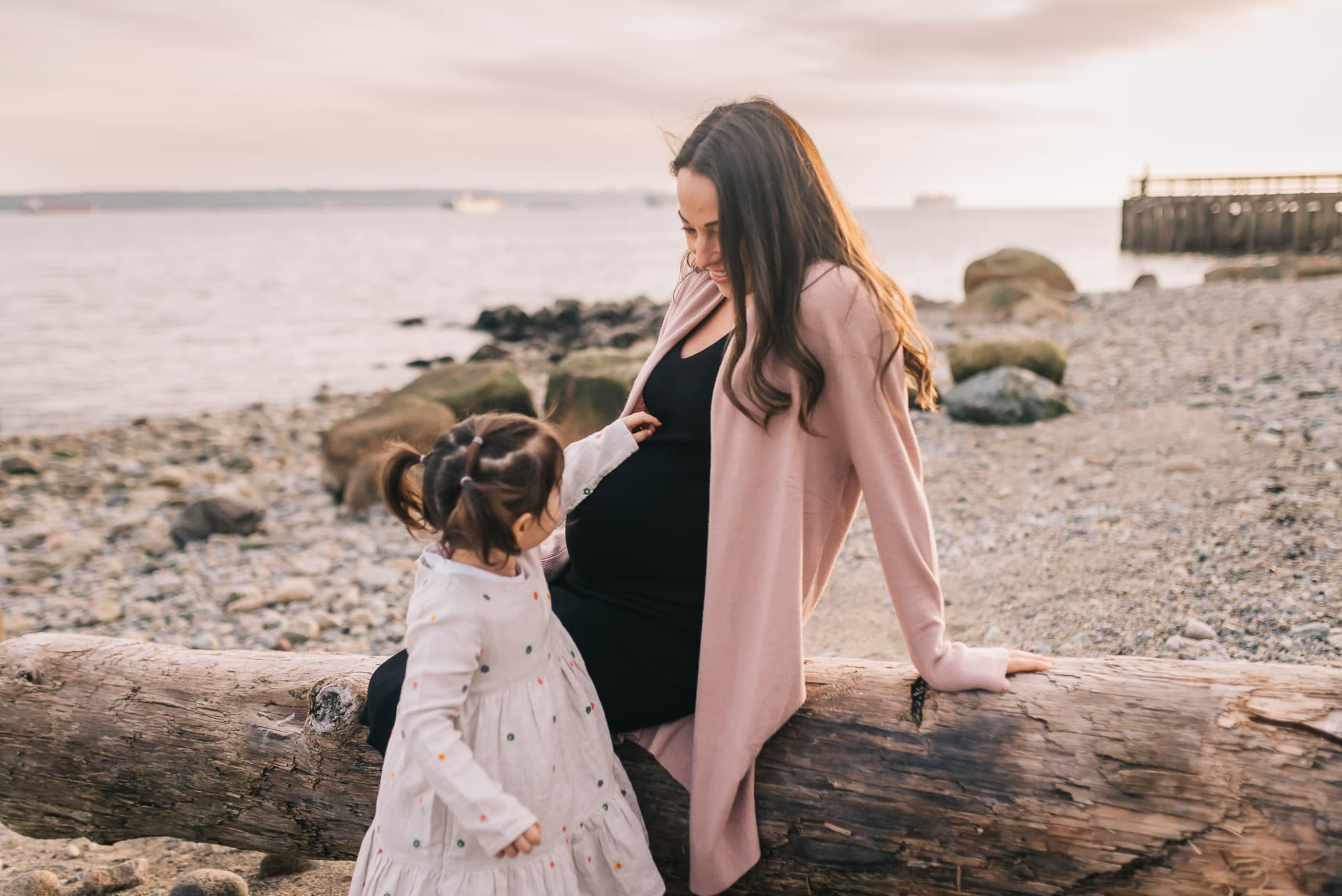 sibling touching mom's pregnant belly on vancouver beach