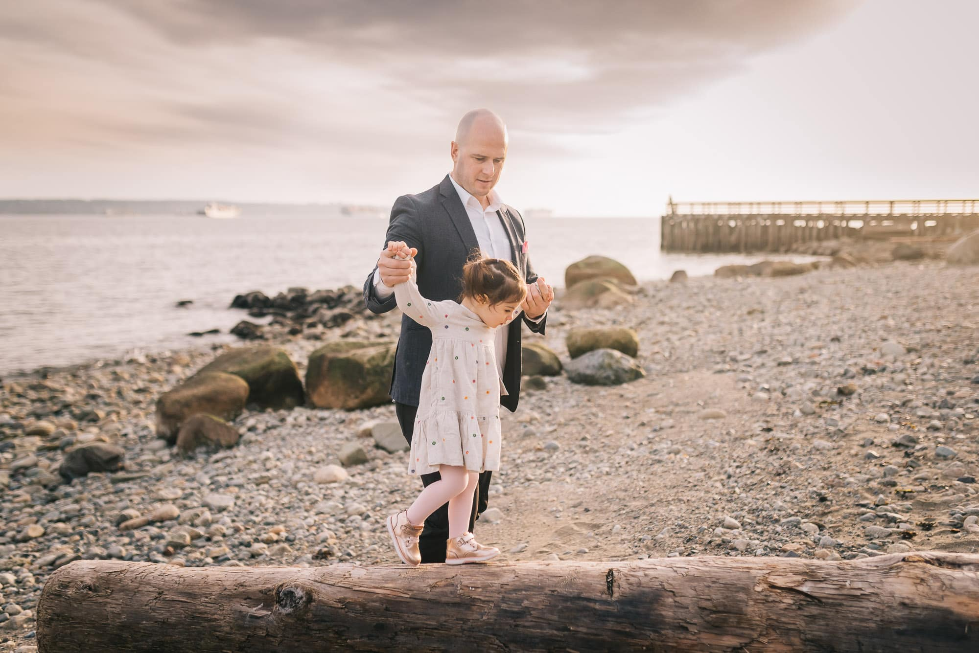dad and daughter balancing on log during Ambleside family photo session